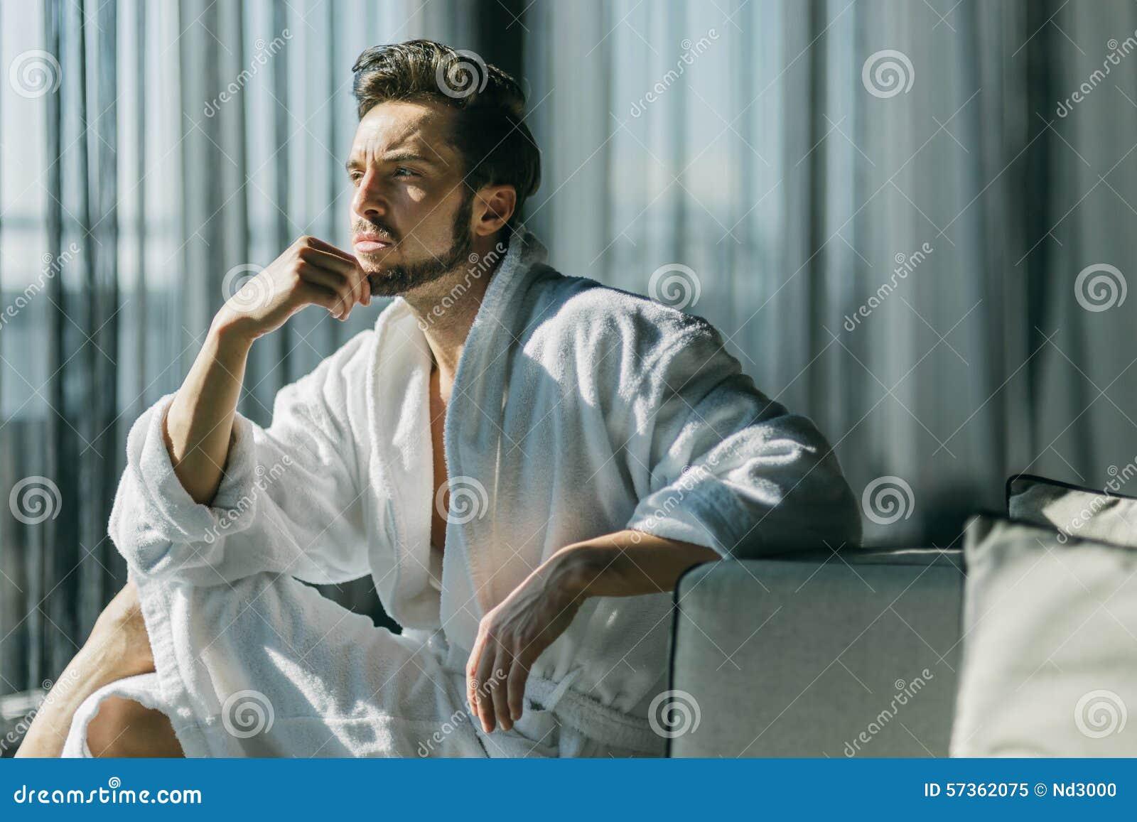 Jonge, knappe mens in de ochtend die terwijl het zitten in r denken