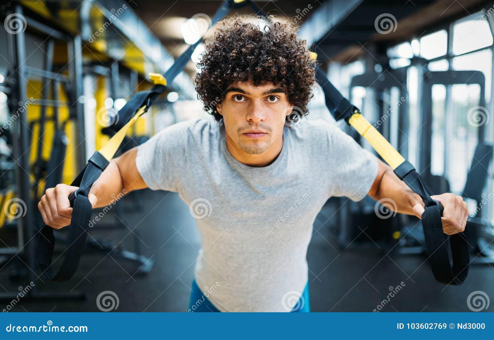 Jonge knappe mens die oefeningen in gymnastiek doen