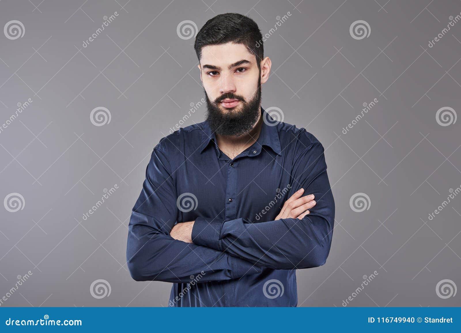 Jonge knappe mens die tegen grijze muur met gekruiste wapens leunen Een ernstige jonge mens met een baard bekijkt de camera