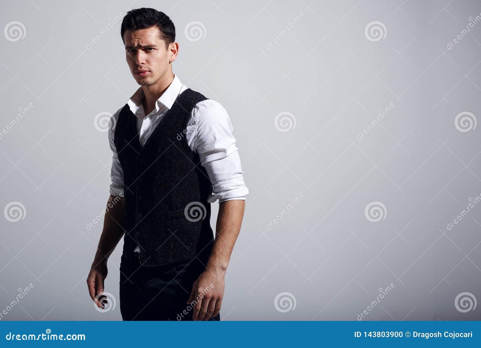 Jonge knappe mens die wit overhemd, zwart vest draagt, dat zich dichtbij grijze muur bevindt