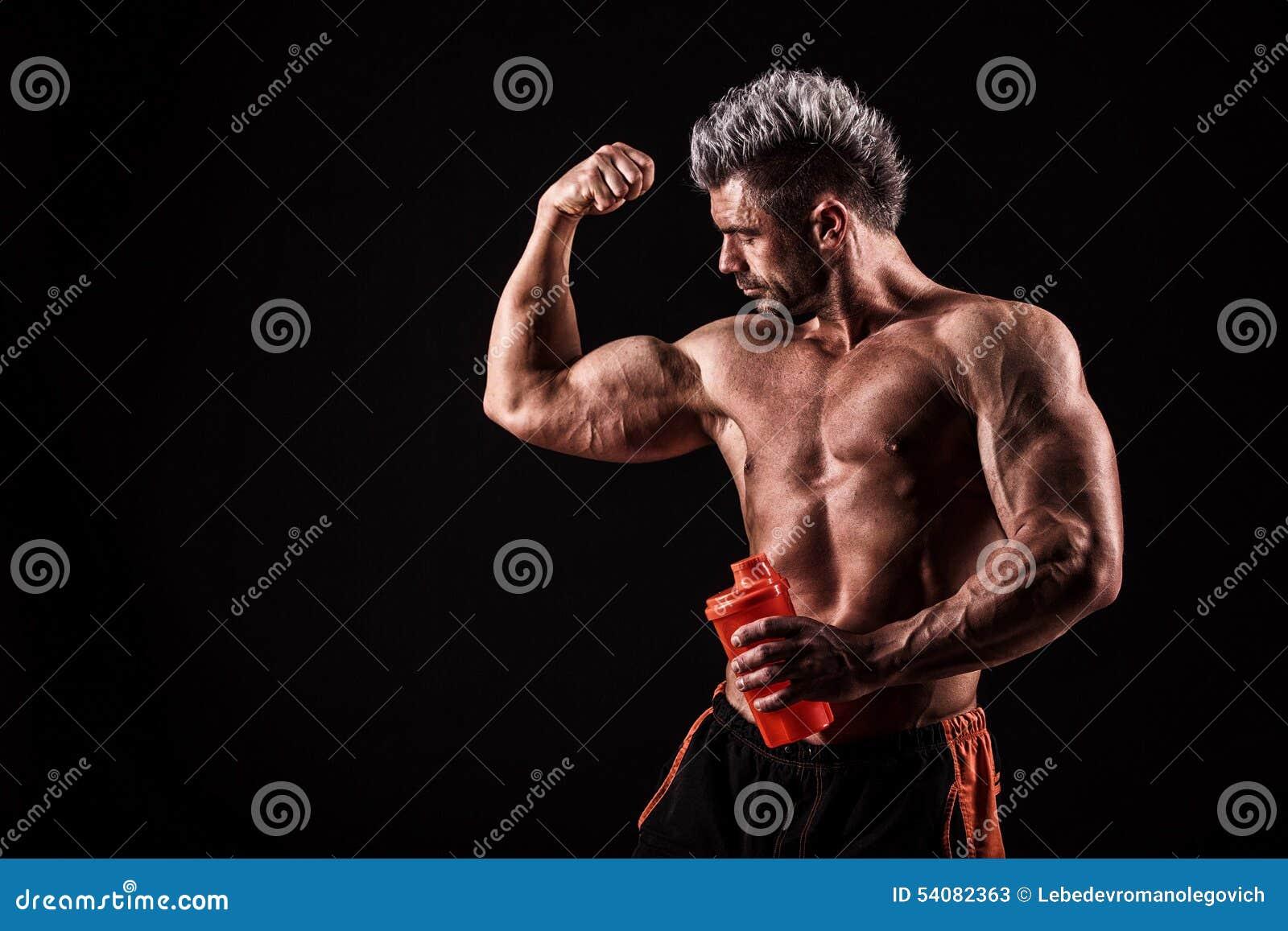 Jonge knappe mens met sterke spieren, eiwitdrank na trai