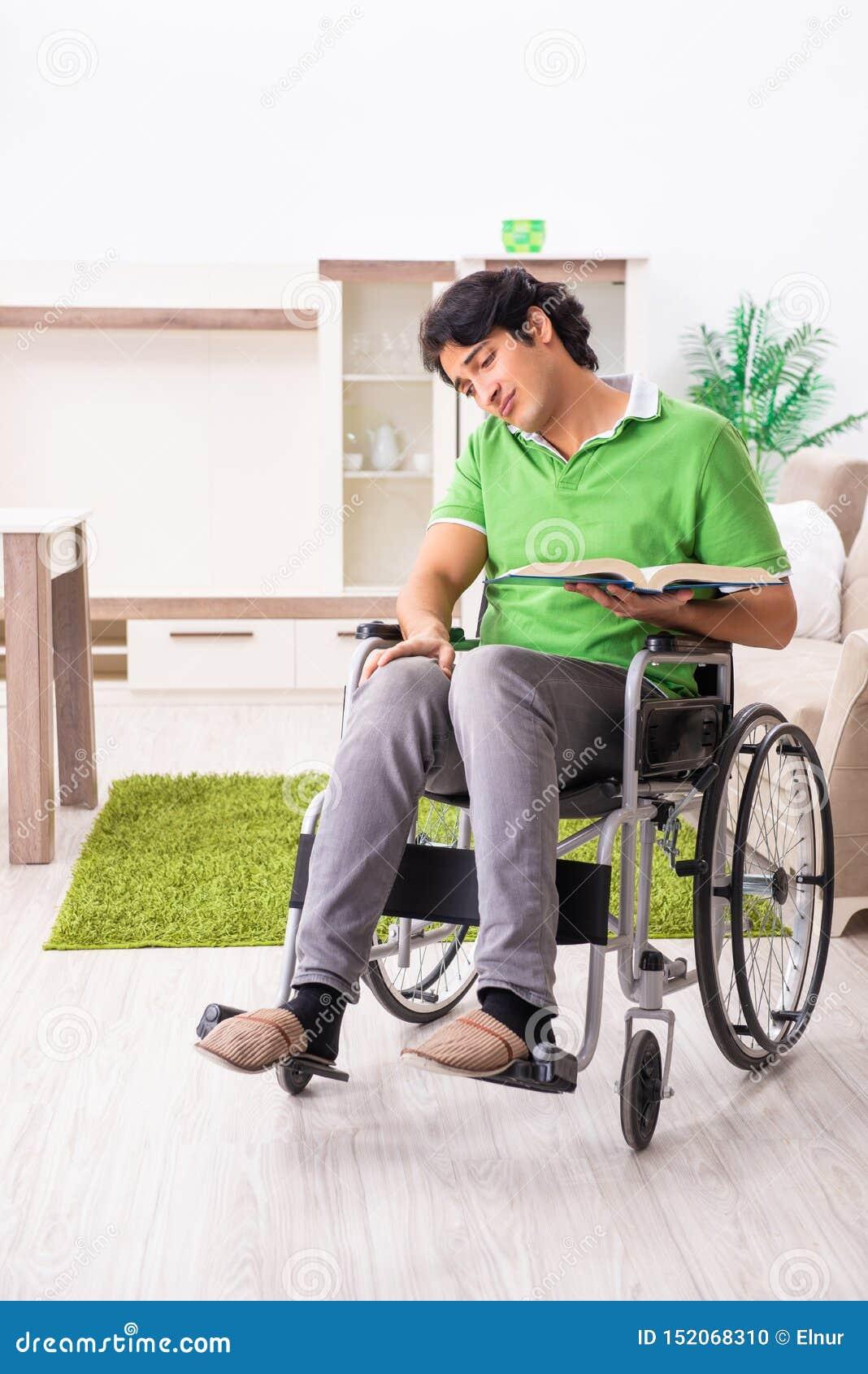Jonge knappe mens in rolstoel thuis