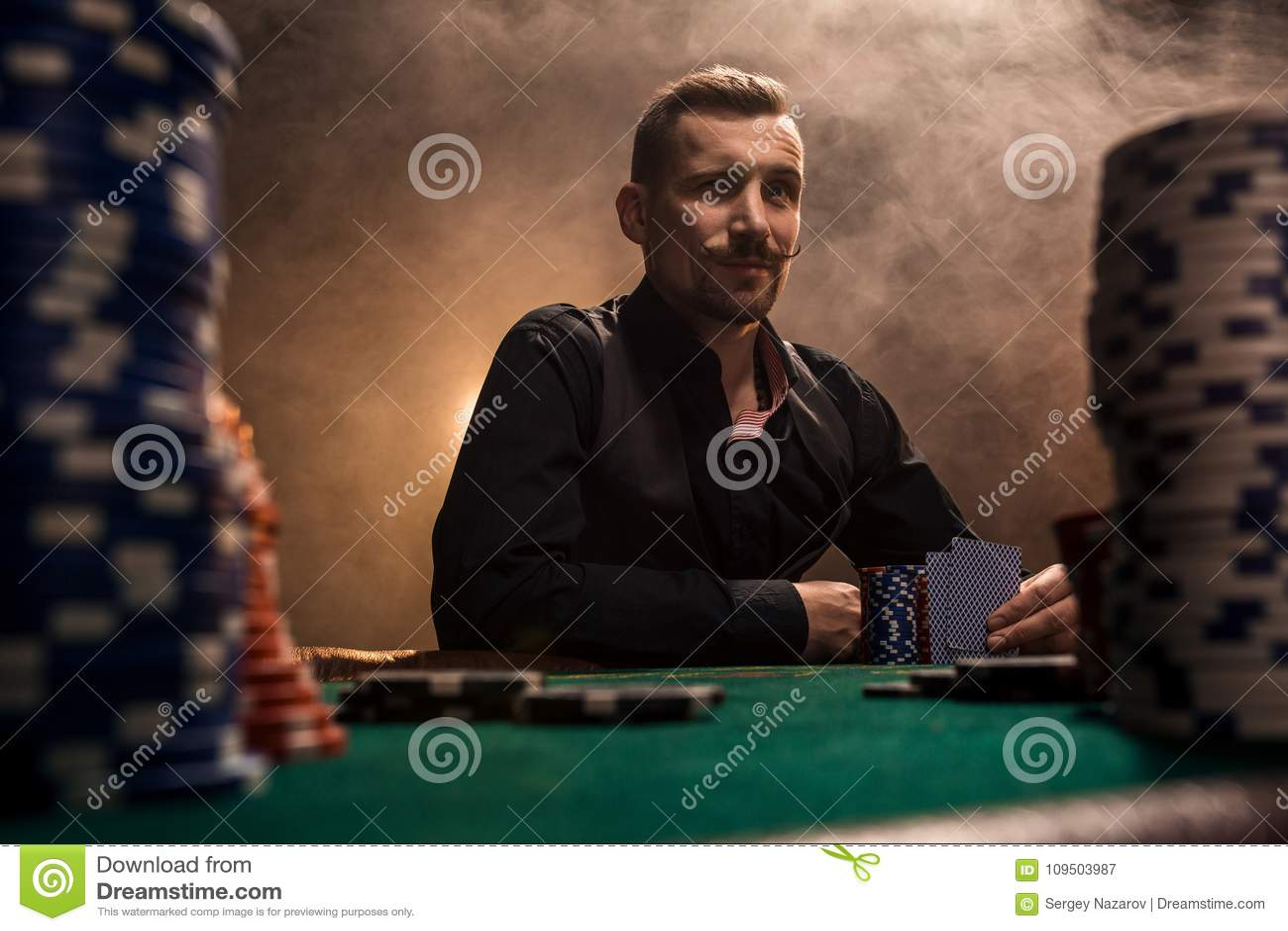 Jonge knappe mensenzitting achter pooklijst met kaarten en spaanders