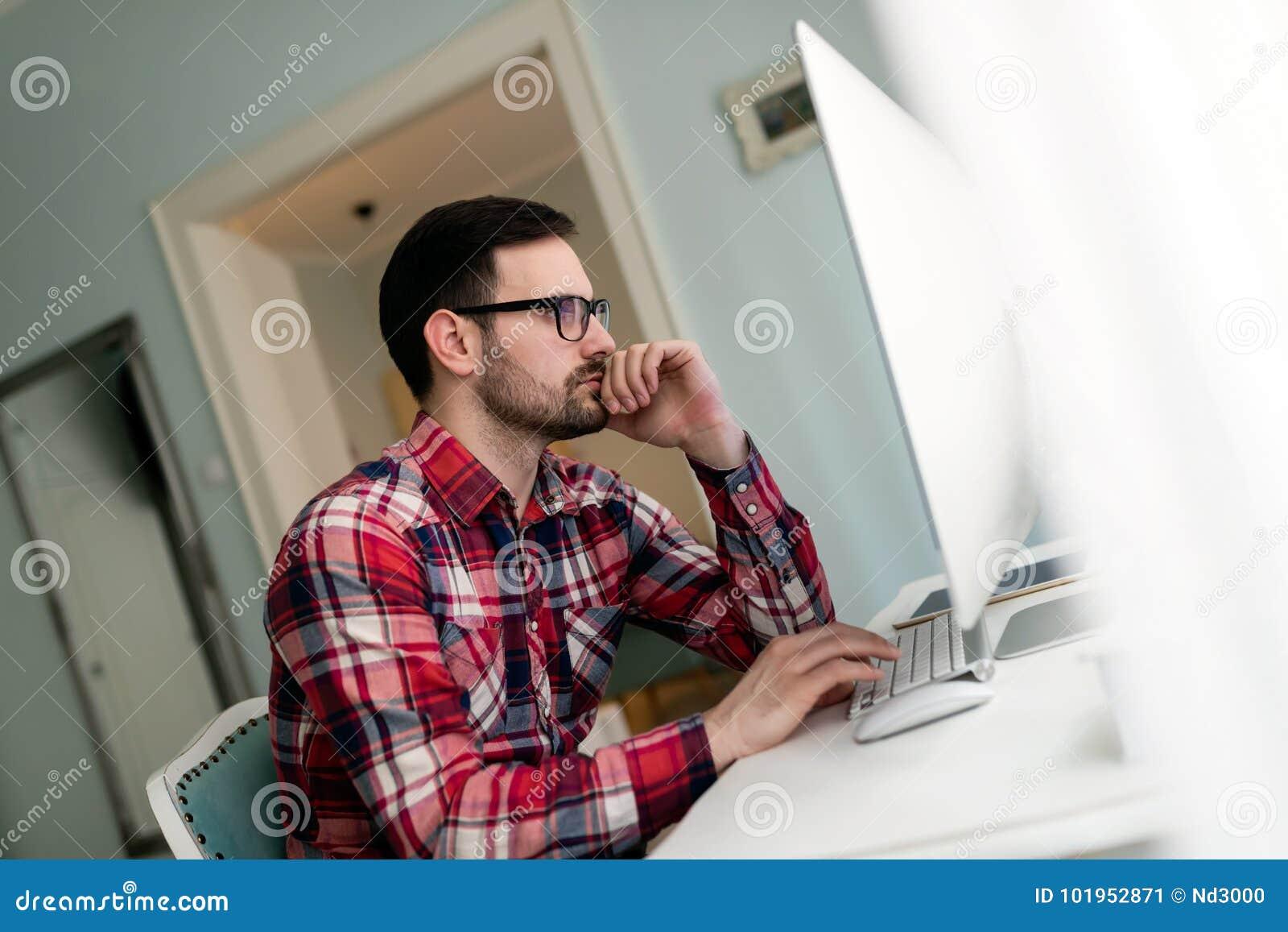 Jonge knappe ontwerper die aan project op computer werken