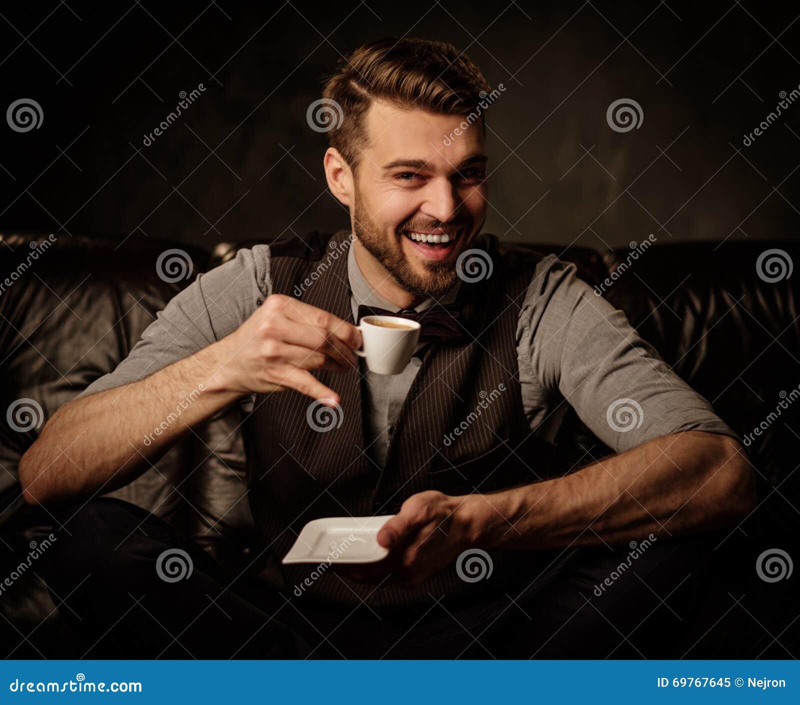Jonge knappe ouderwetse gebaarde mens die pret met kop van koffie op comfortabele leerbank hebben op donkere achtergrond