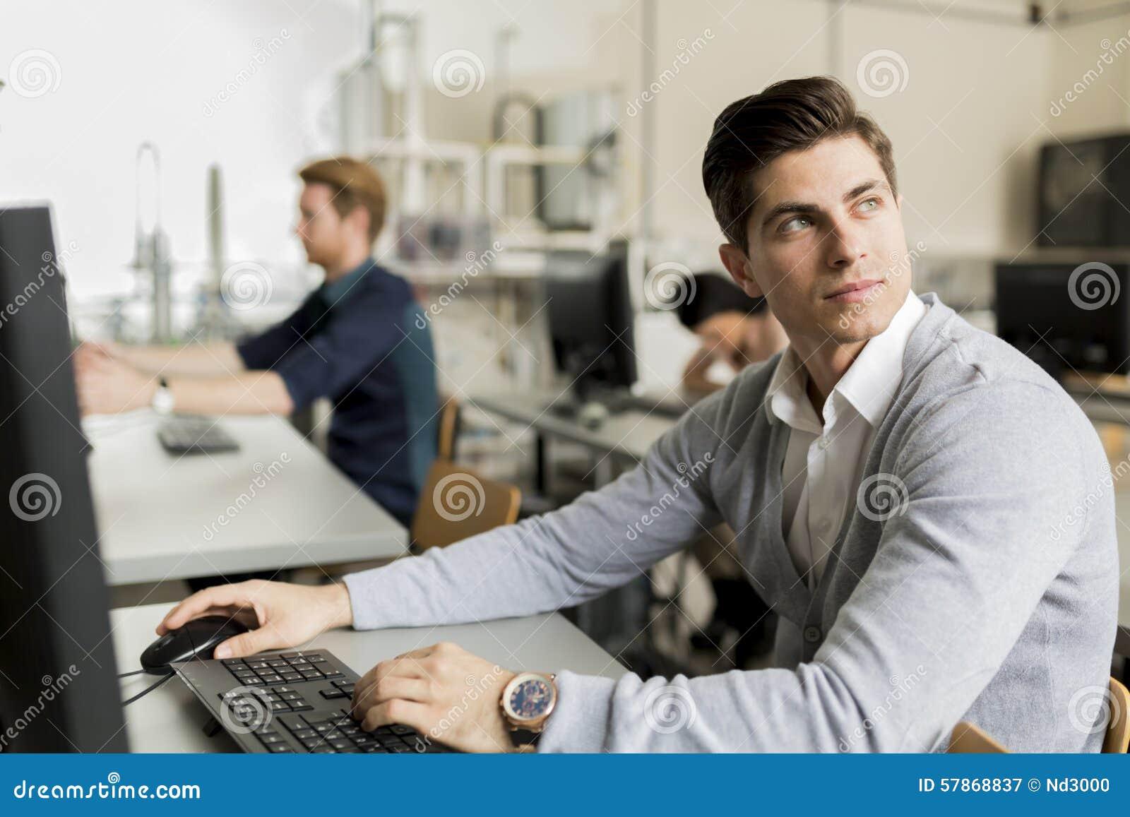 Jonge knappe student die computer met behulp van