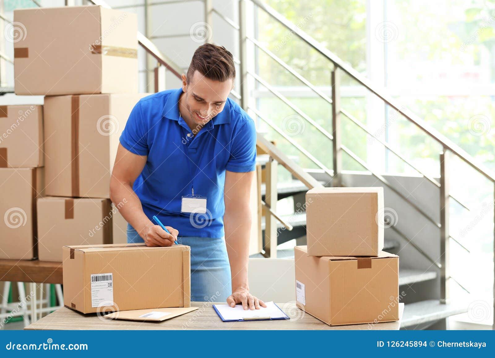 Jonge koerier die nota s over pakketten maken bij leveringsafdeling