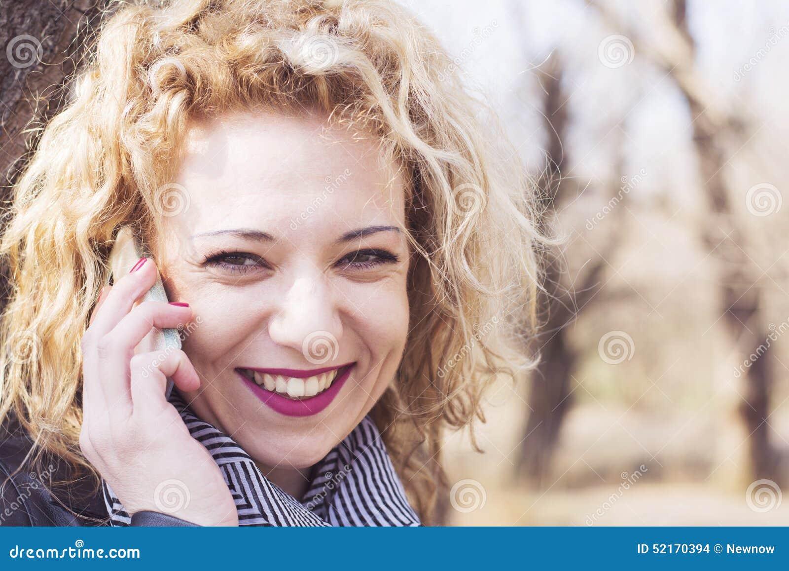 Jonge krullende blonde vrouw die op de telefoon in openlucht spreken in