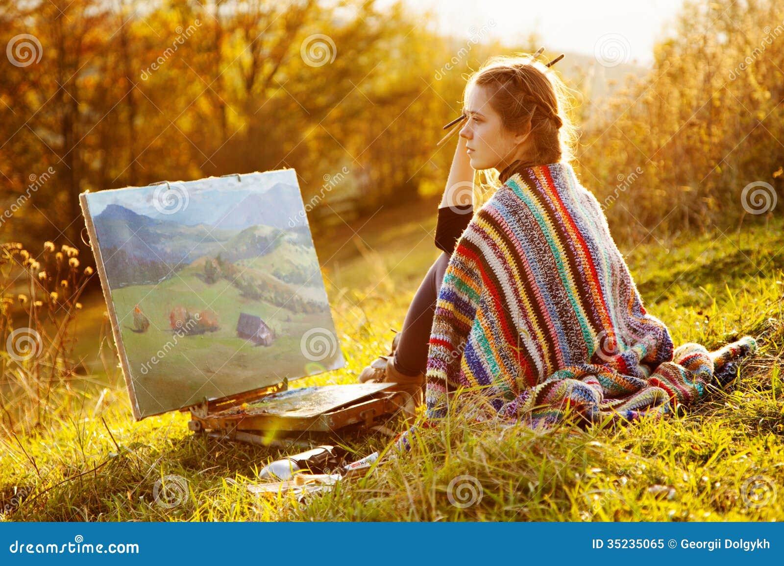 Jonge kunstenaar die een de herfstlandschap schildert