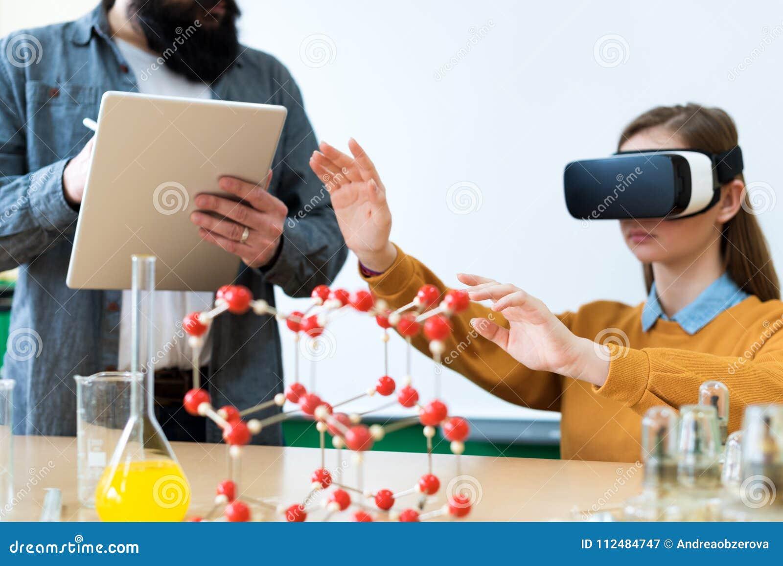 Jonge leraar die Virtuele Werkelijkheidsglazen en 3D presentatie gebruiken om studenten in chemieklasse te onderwijzen Onderwijs,