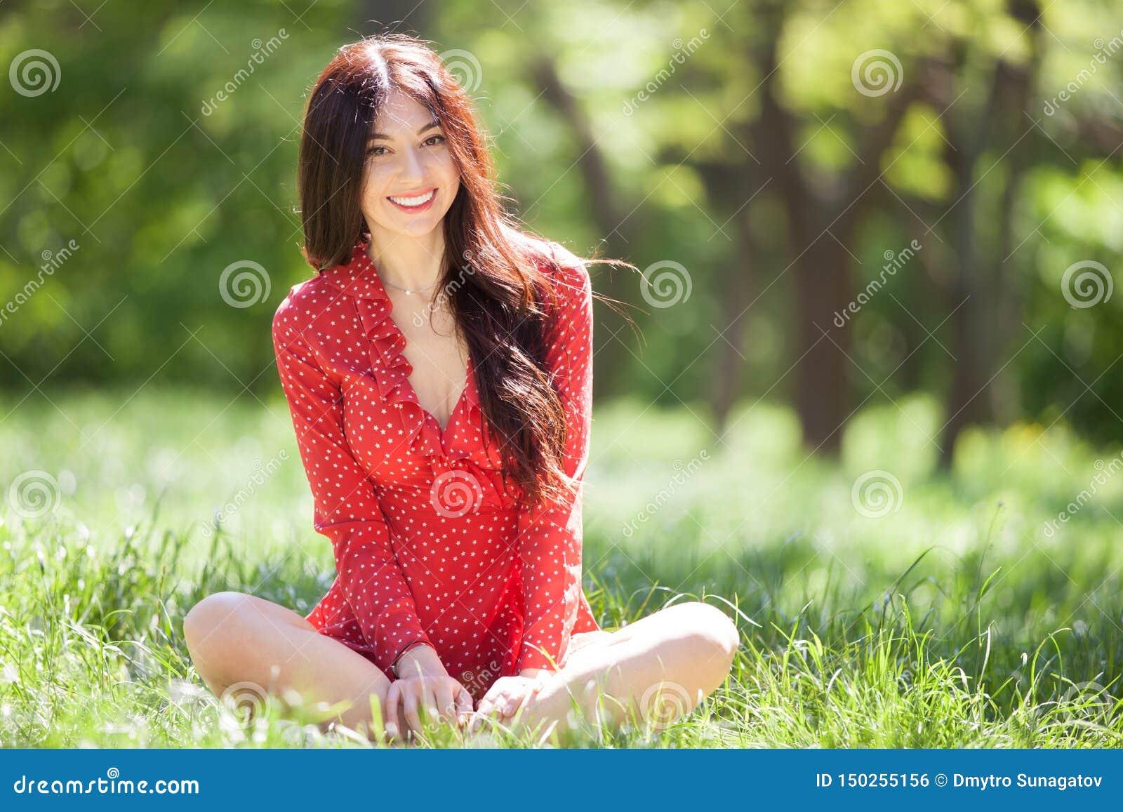 Jonge leuke vrouw in het rode kleding ontspannen in het park De sc?ne van de schoonheidsaard met kleurrijke achtergrond, bomen bi