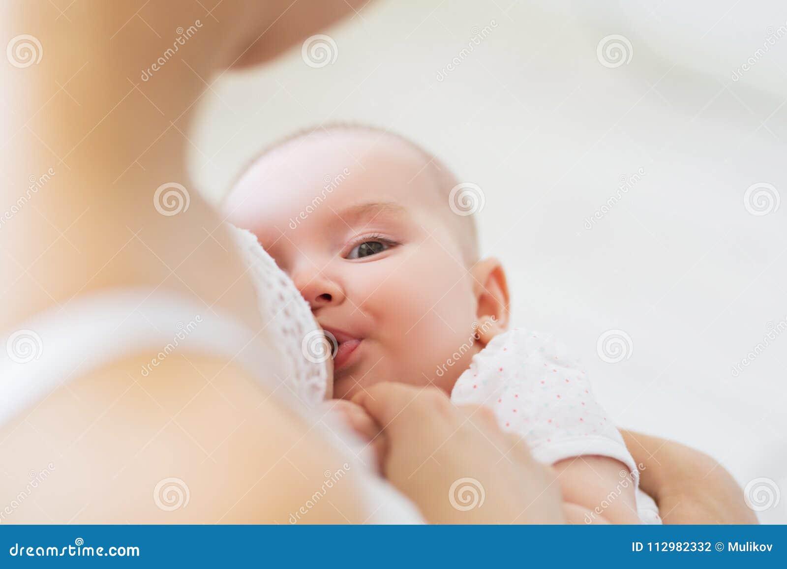 Jonge mammaborst die - haar pasgeboren kind voeden Het concept van de lactatiezuigeling Moedervoer haar babyzoon of dochter met m