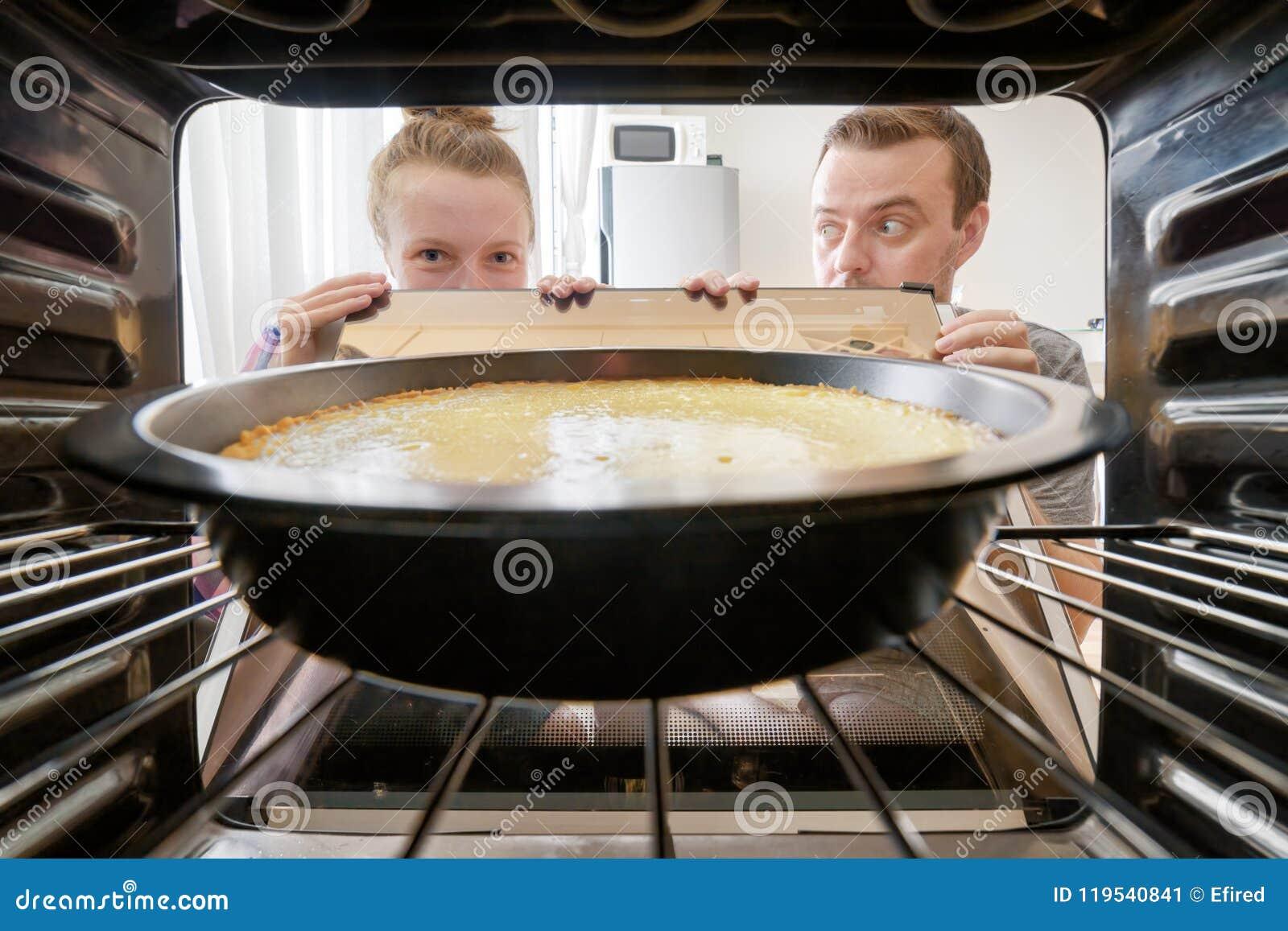 Jonge man die bij vrouw staren die die kaastaart bekijken