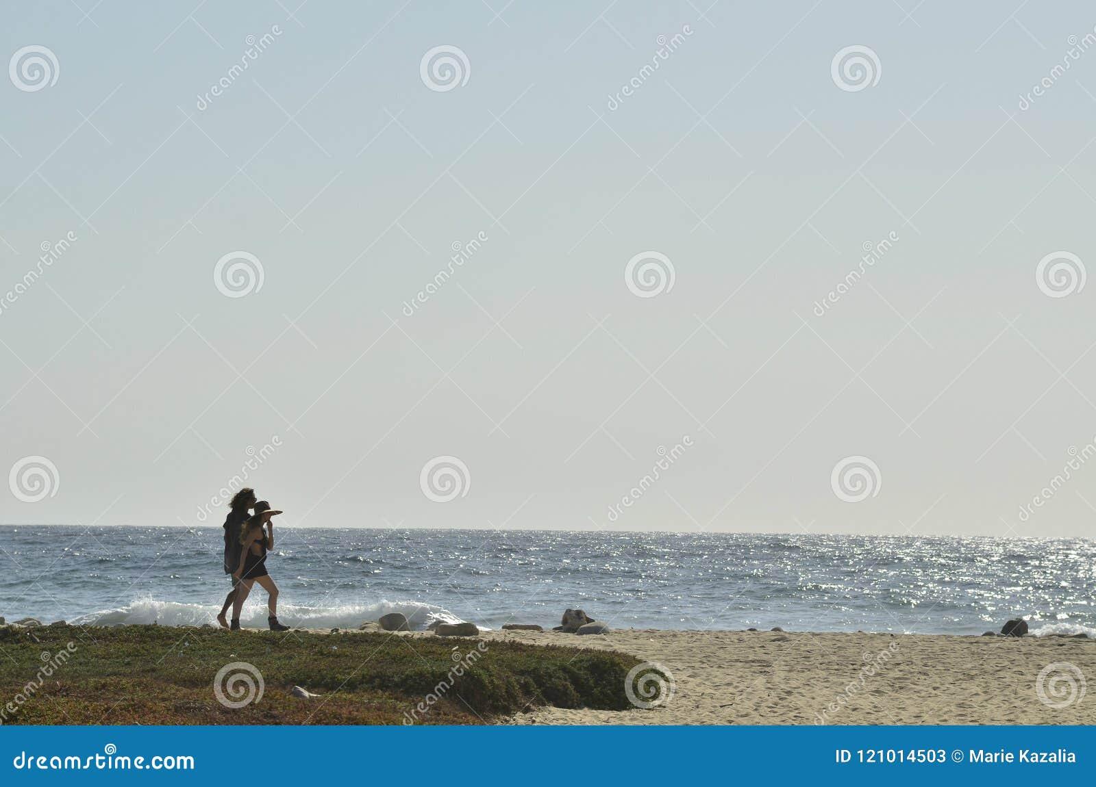 Jonge man en vrouwen het paar silhouetteert het lopen Vreedzaam strand Baja, Mexico