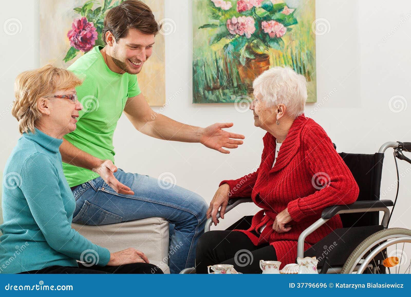 Jonge Man Het Tallking Met Twee Oudere Vrouwen Stock Foto