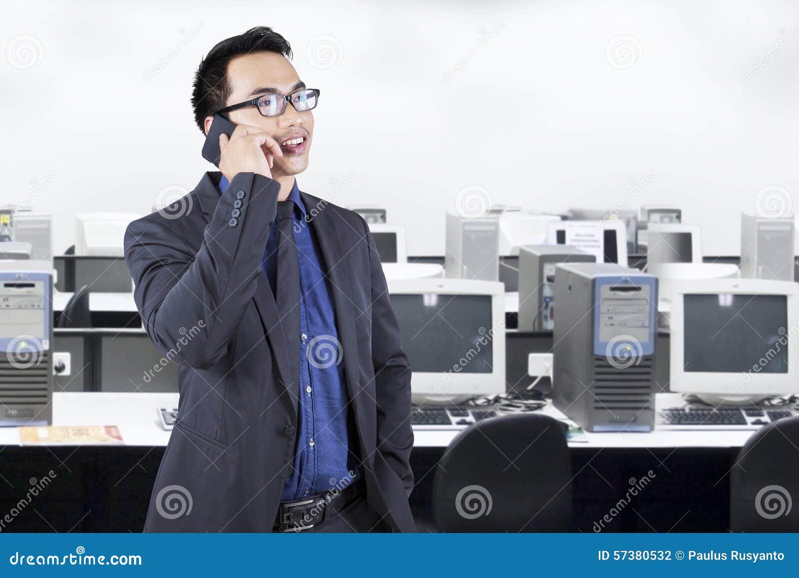 Jonge manager die op de telefoon in bureau spreken