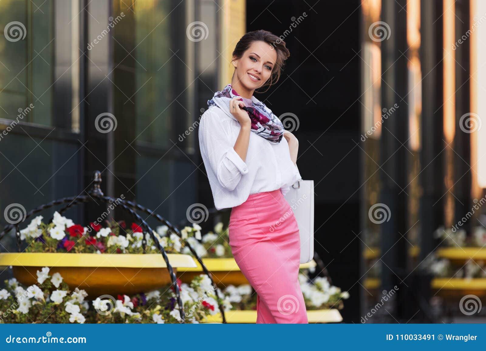 Jonge manier bedrijfsvrouw in wit overhemd en roze potloodrok