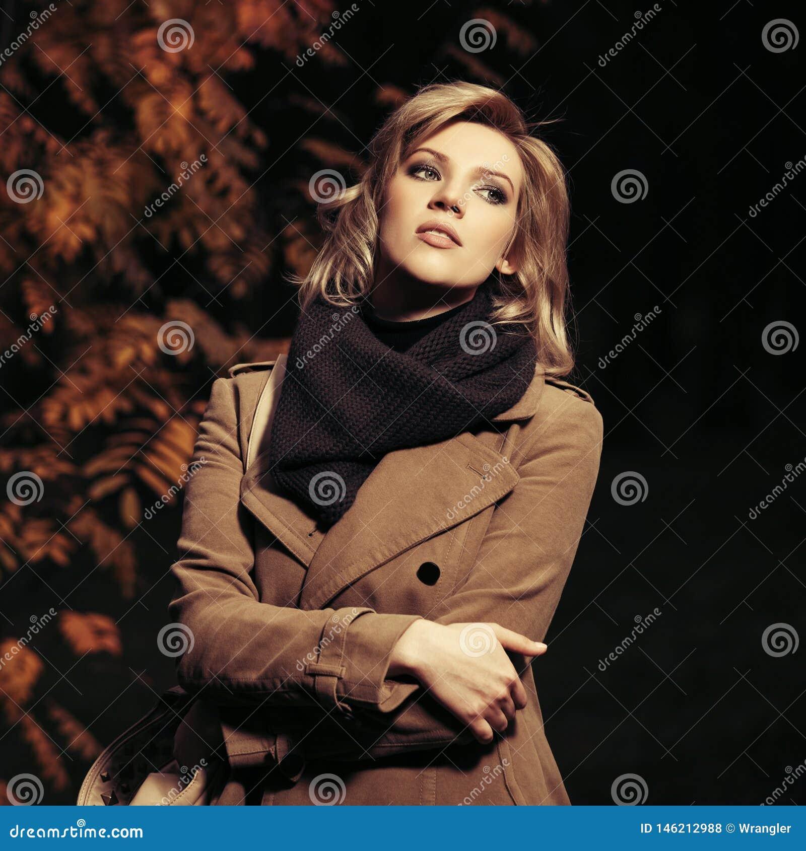 Jonge maniervrouw die in beige laag in het park van de de herfststad bij nacht lopen