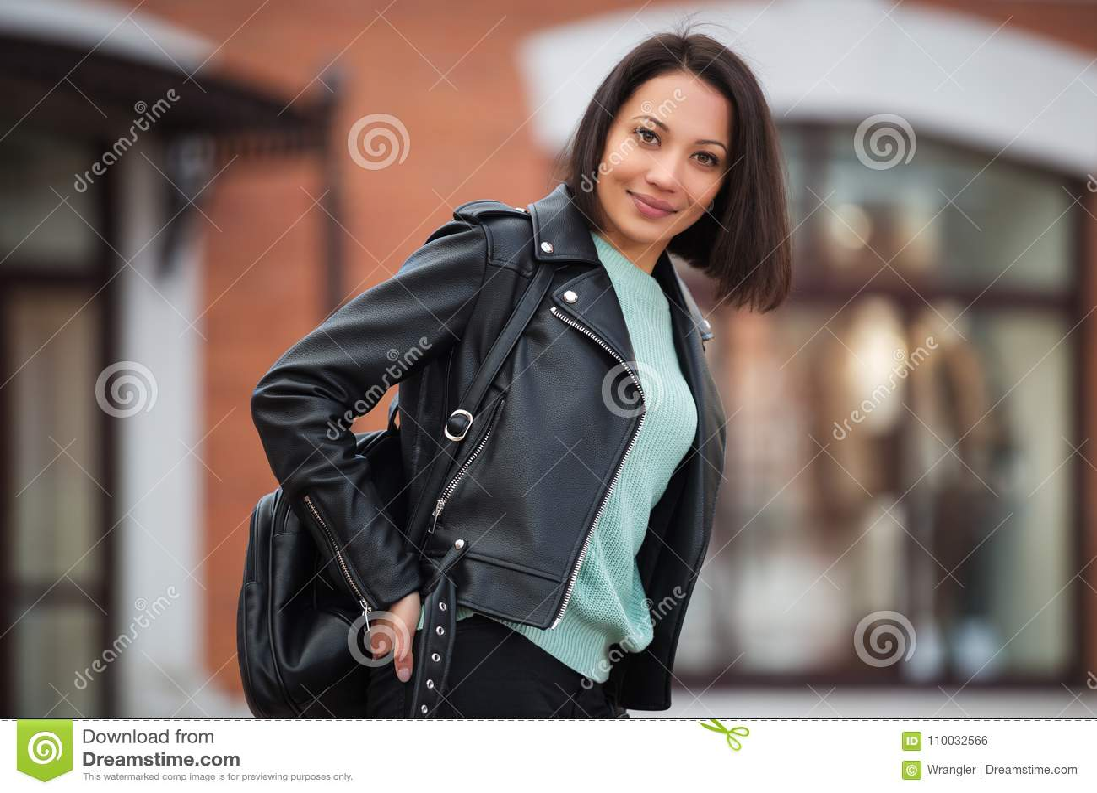 Jonge maniervrouw die in zwart leerjasje in stadsstraat lopen