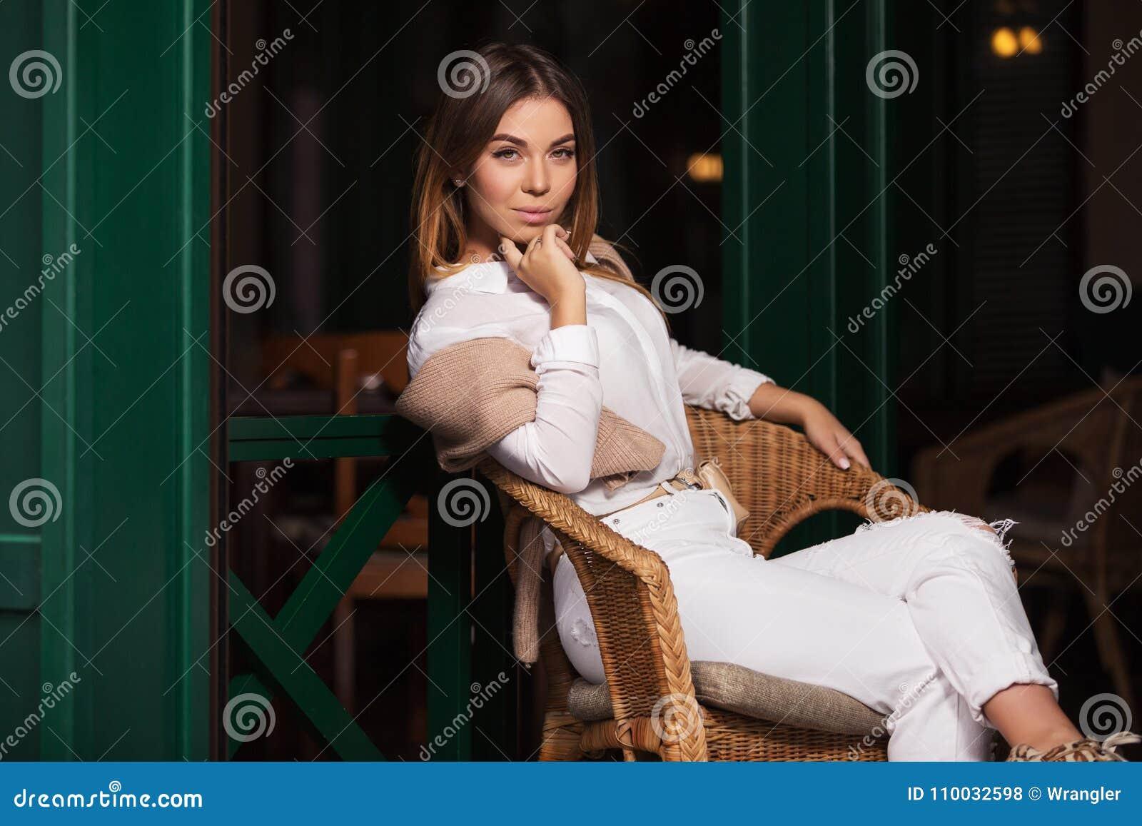 Jonge maniervrouw in witte overhemdszitting op rieten stoel