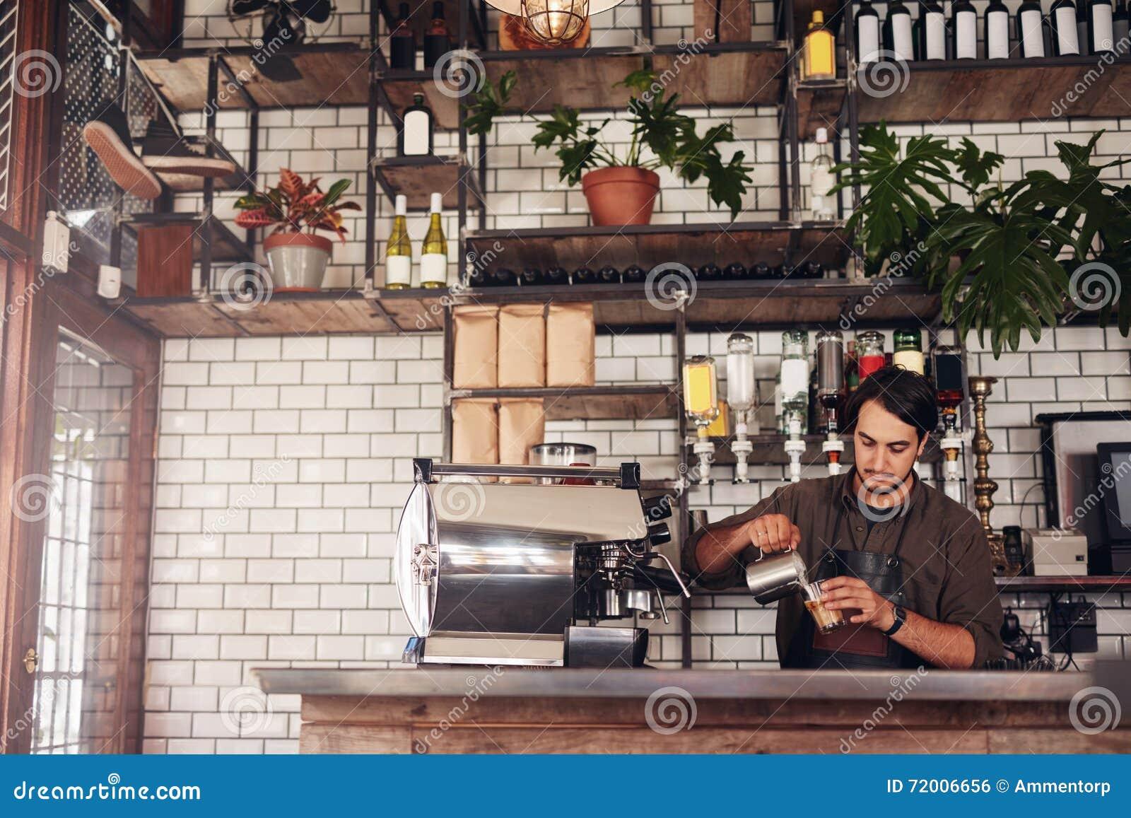 Jonge mannelijke barista die een kop van koffie maken