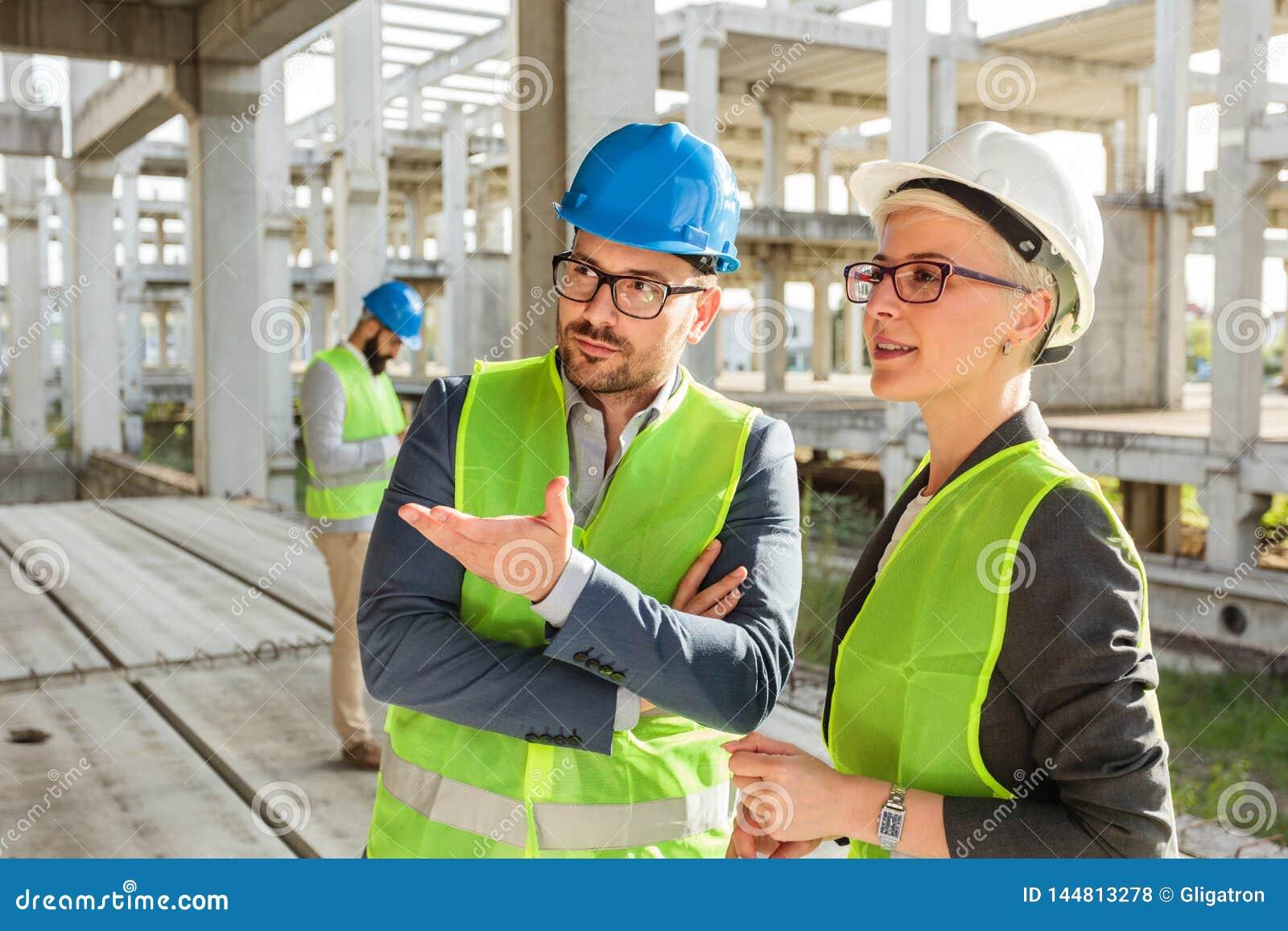 Jonge mannelijke en vrouwelijke architecten of partners die en op een bouwwerf spreken bespreken