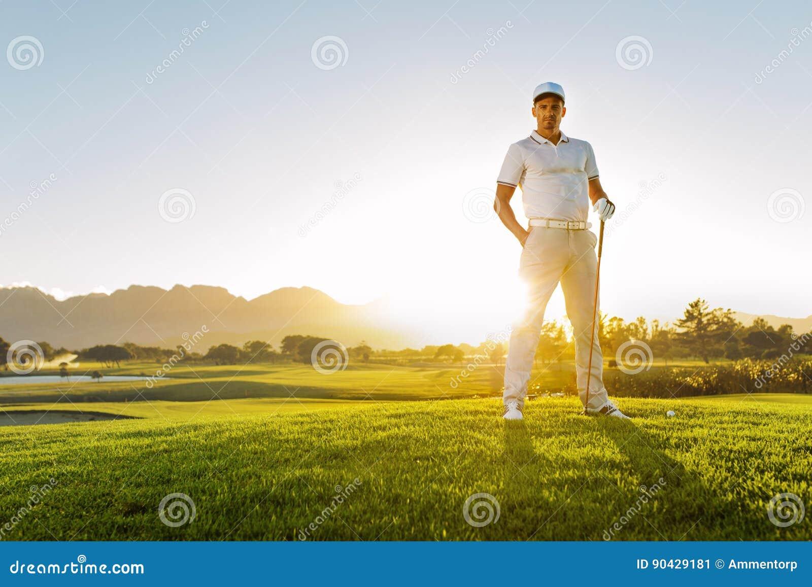 Jonge mannelijke golfspeler die zich op golfcursus bevinden op een de zomerdag