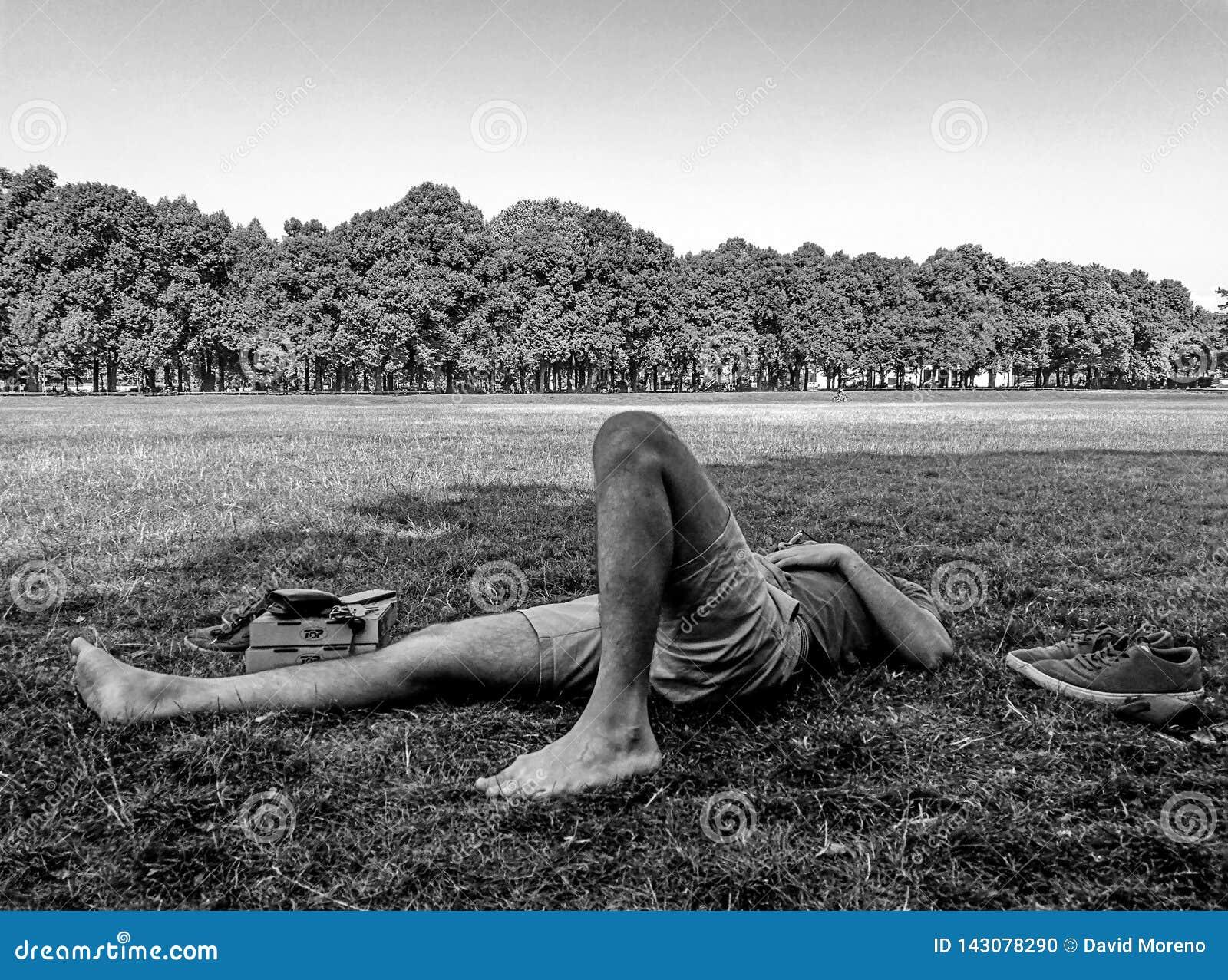 Jonge mannelijke schaatser die op het gras met zijn gesloten ogen rusten