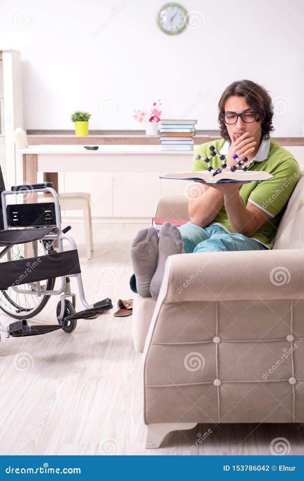 Jonge mannelijke student in rolstoel thuis