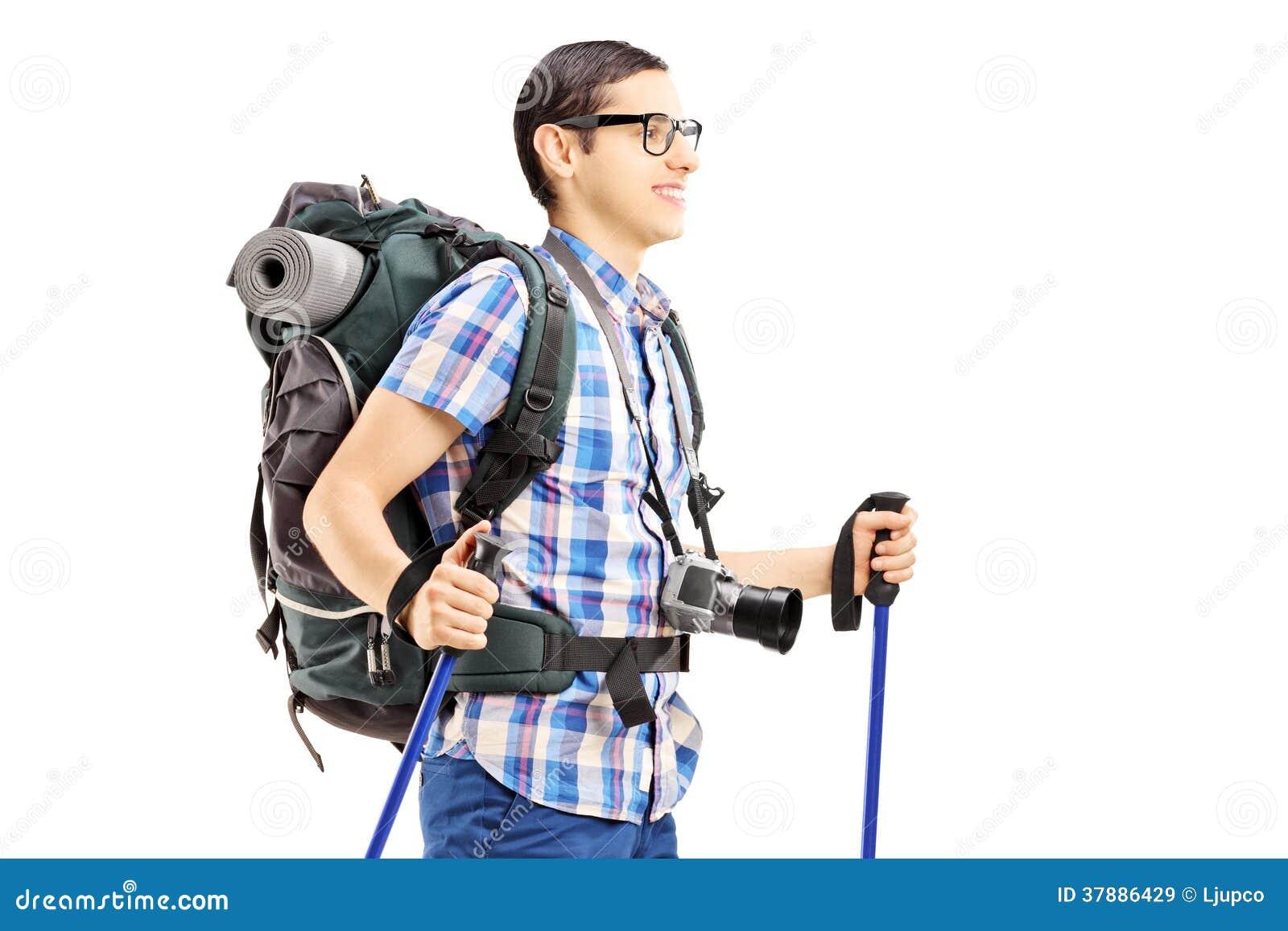 Jonge mannelijke toerist die met wandelingspolen lopen