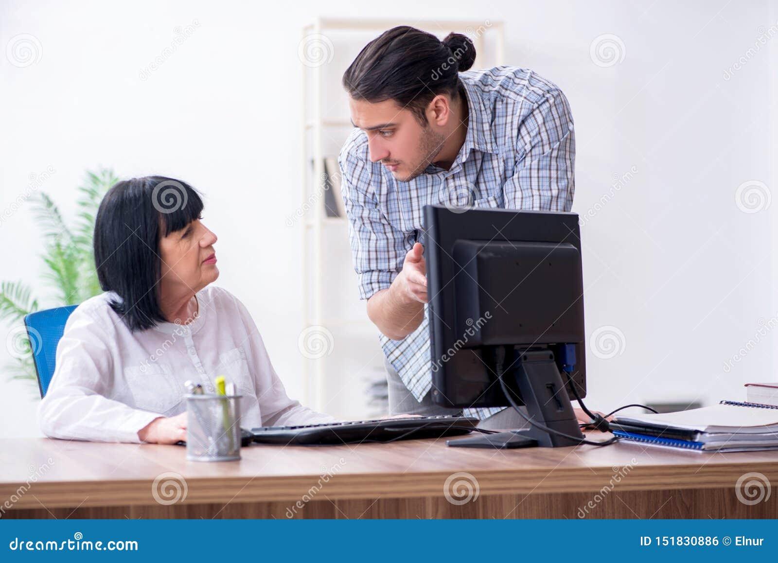 Jonge mannelijke werknemer die aan oude vrouwelijke collega hoe te ons verklaren