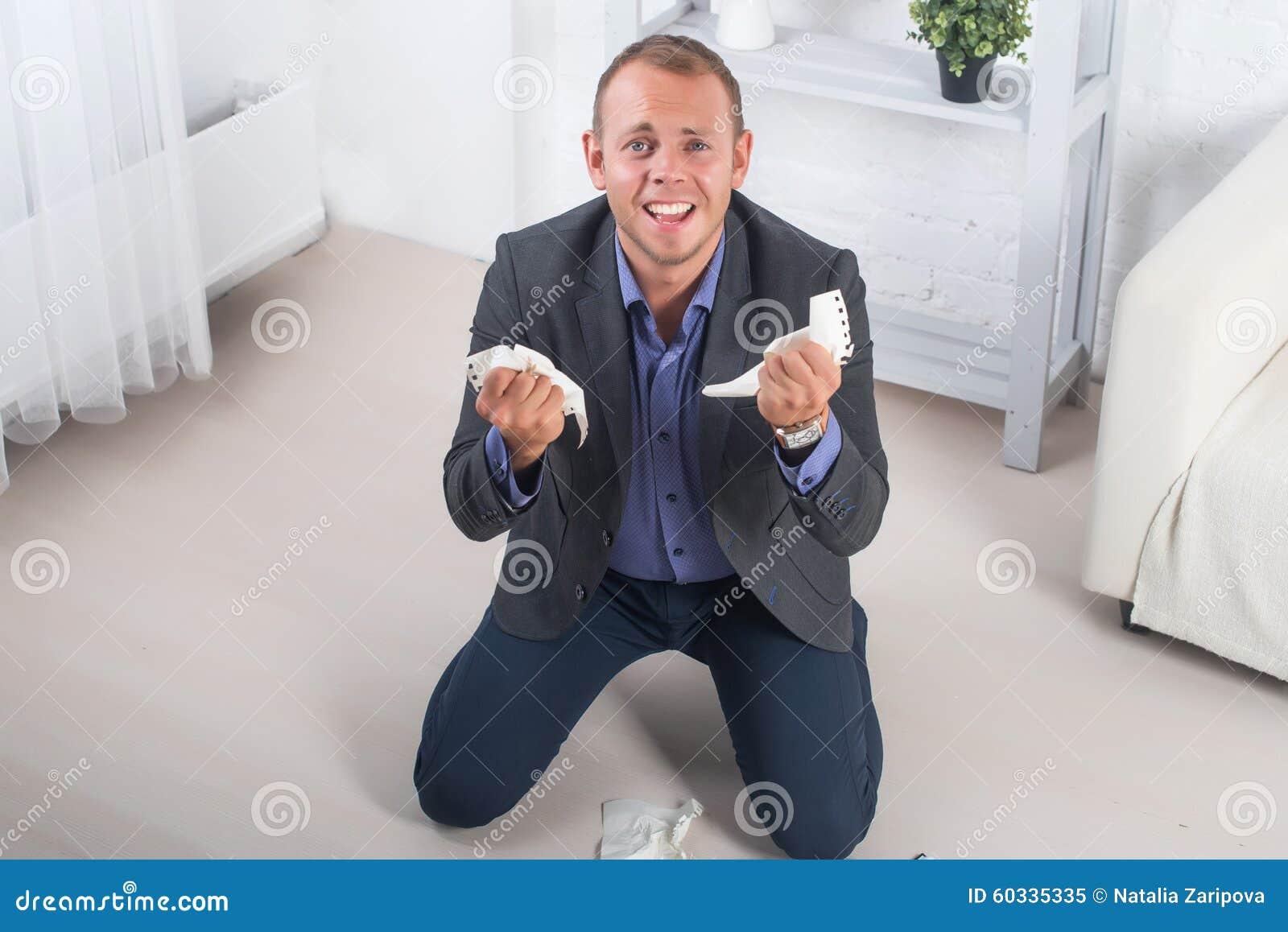 Jonge mannelijke zakenmanwoede, het hysterische knielen op de vloer, het gillen van en het houden van verfrommeld document in zij
