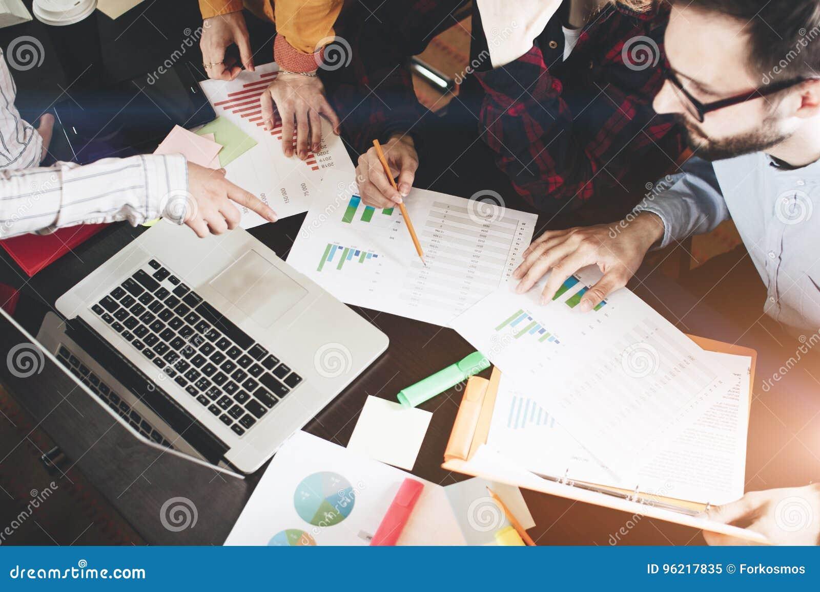 Jonge medewerkers grafieken bespreken en grafieken die de resultaten van hun succesvol groepswerk tonen