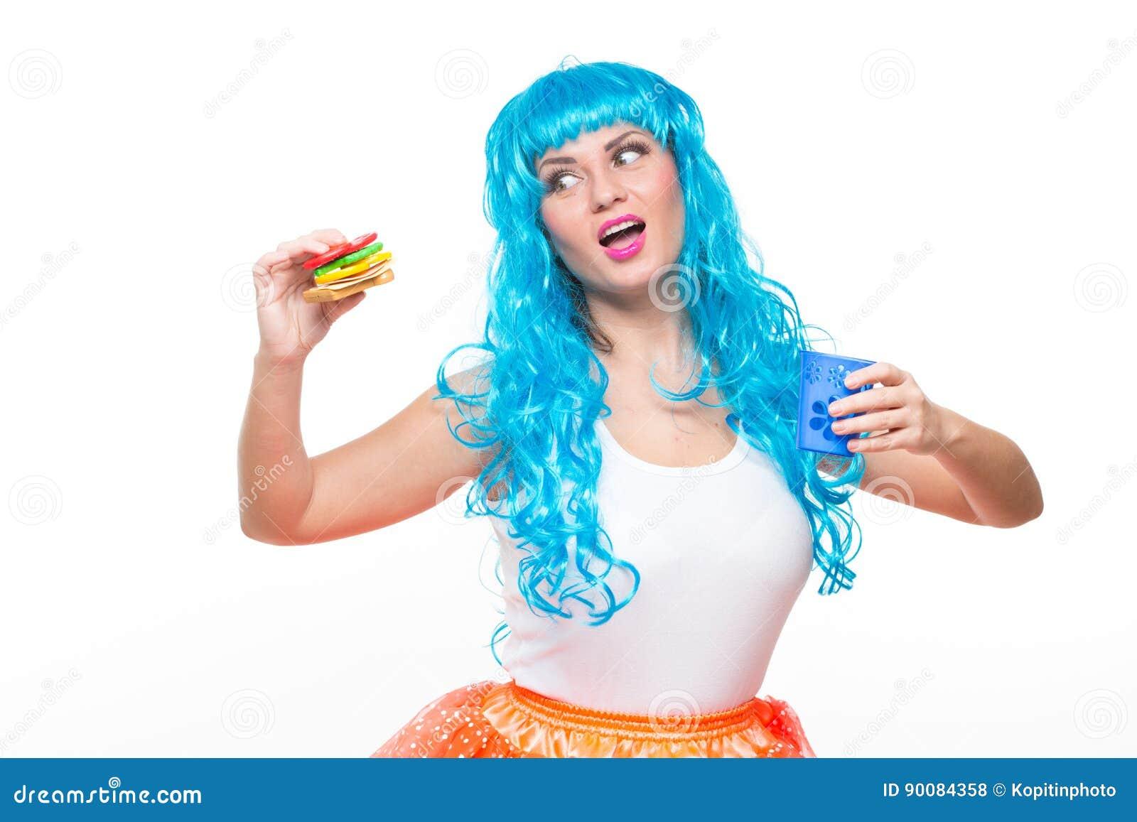 Jonge meisjespop met blauw haar plastiek die een sandwich eten honger