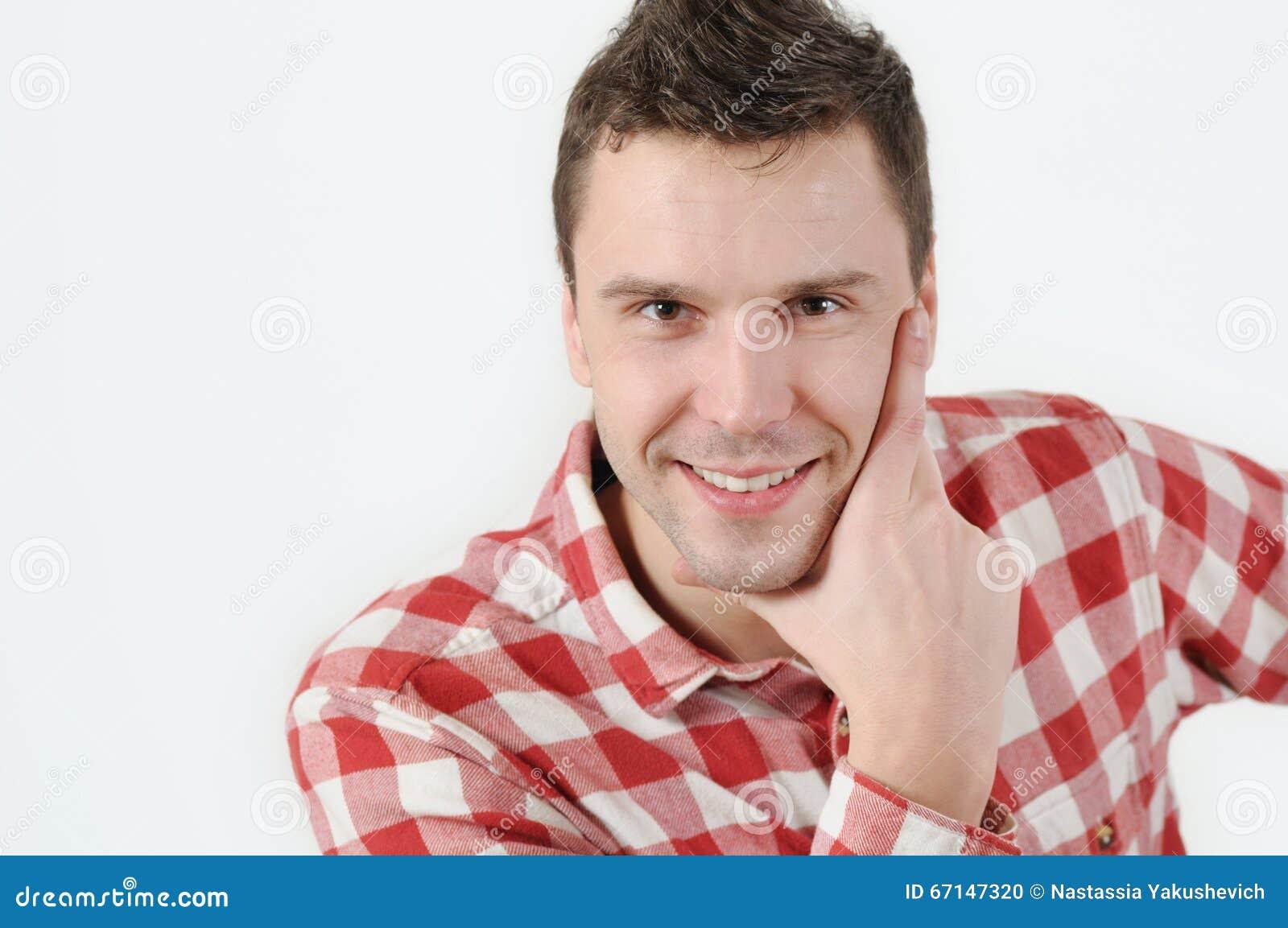 Jonge mens in de holdingshand van het hipsteroverhemd op kin en status tegen witte achtergrond