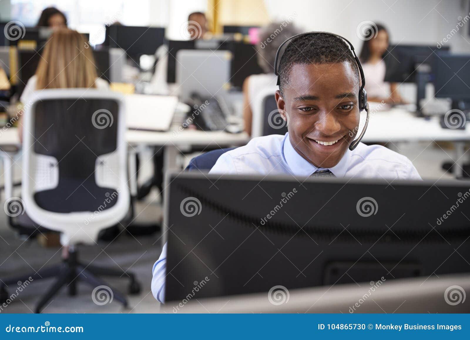 Jonge mens die bij computer met hoofdtelefoon in bezig bureau werken
