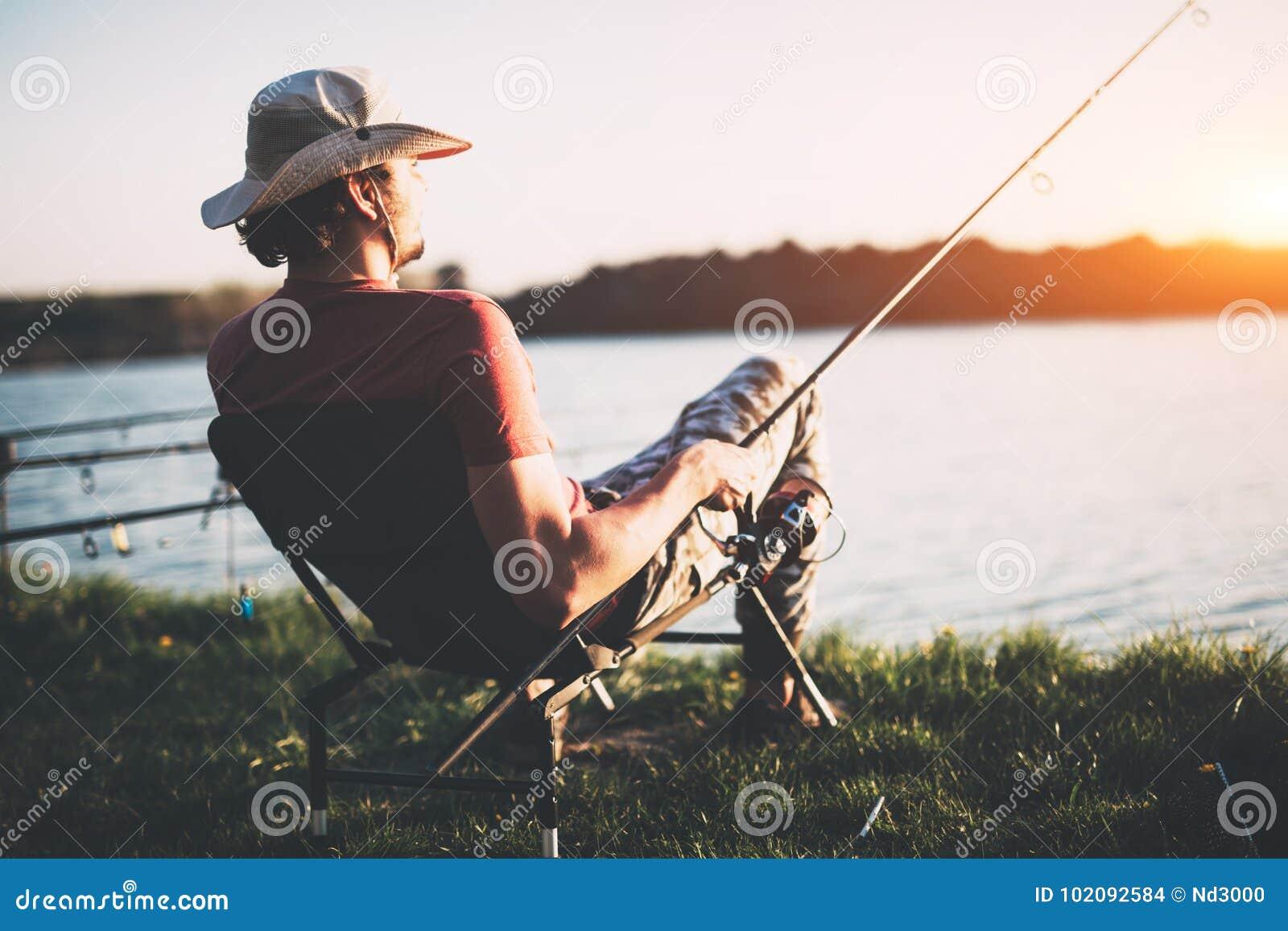 Jonge mens die bij vijver vist en van hobby geniet