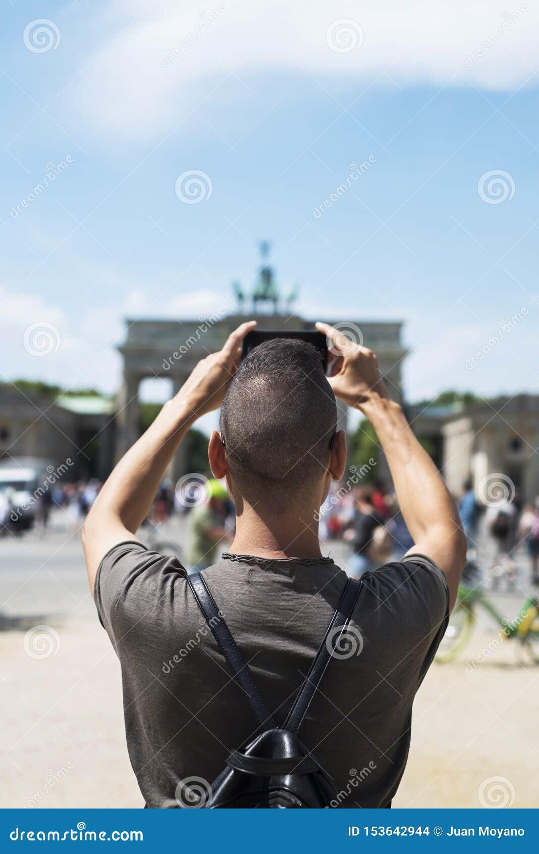 Jonge mens die een beeld van de Poort van Brandenburg nemen