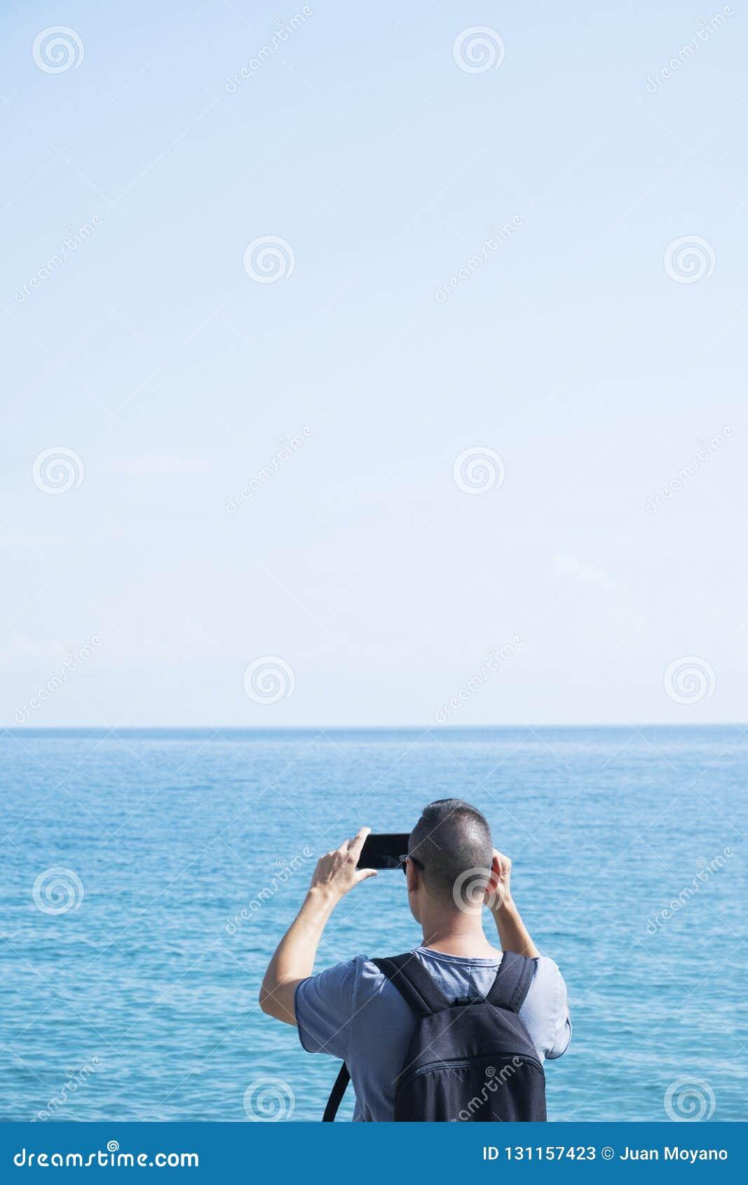 Jonge mens die een foto van het overzees nemen