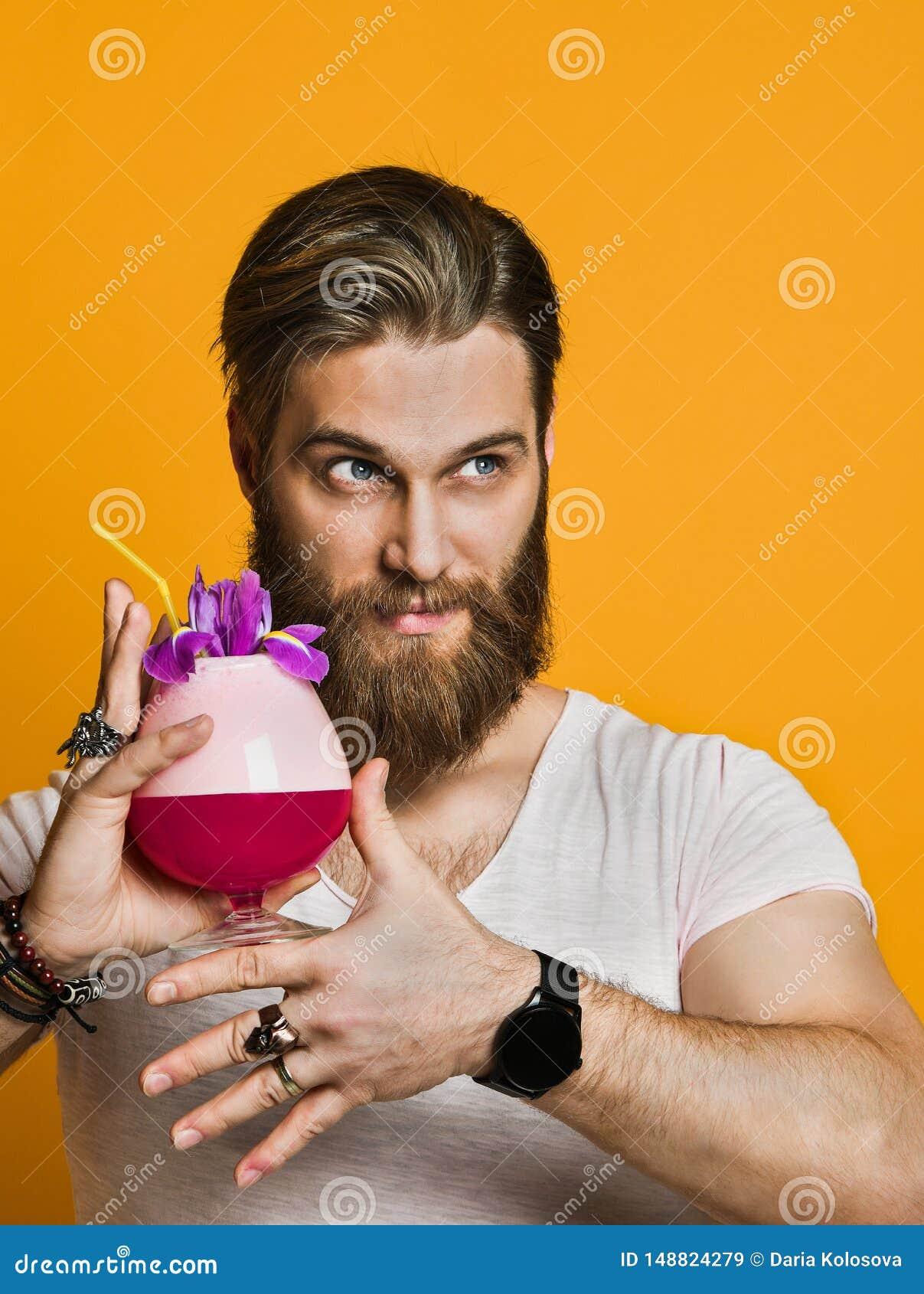Jonge mens die een multicolored cocktail houden
