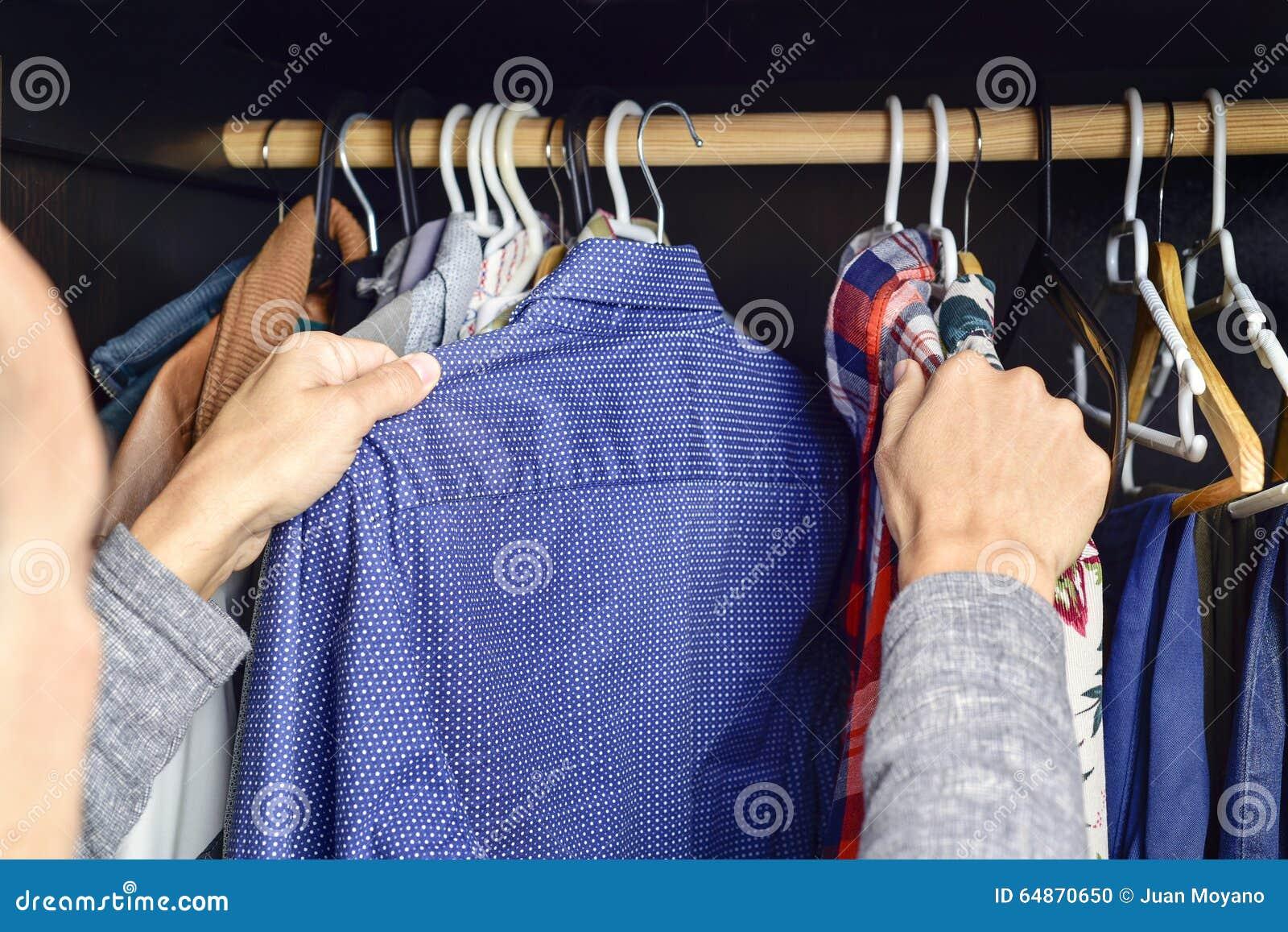 Jonge mens die een overhemd kiezen van een klerenrek