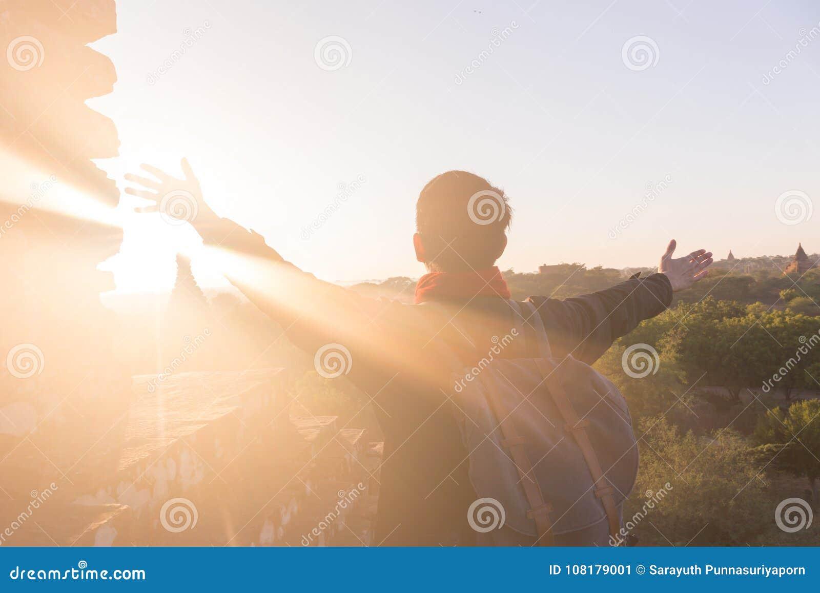 Jonge mens die handen opheffen omhoog tegen zonlicht - vermelde succes, voltooiing en overwinning