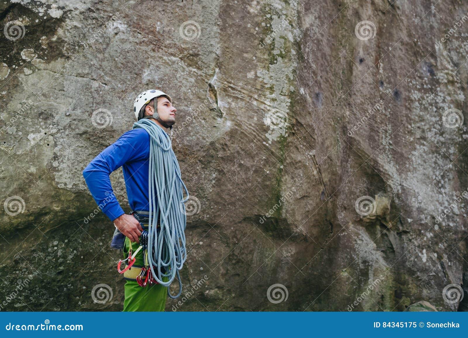 Jonge mens die in het beklimmen van materiaal met kabel dragen die zich voor een steenrots bevinden en voorbereidingen treffen te
