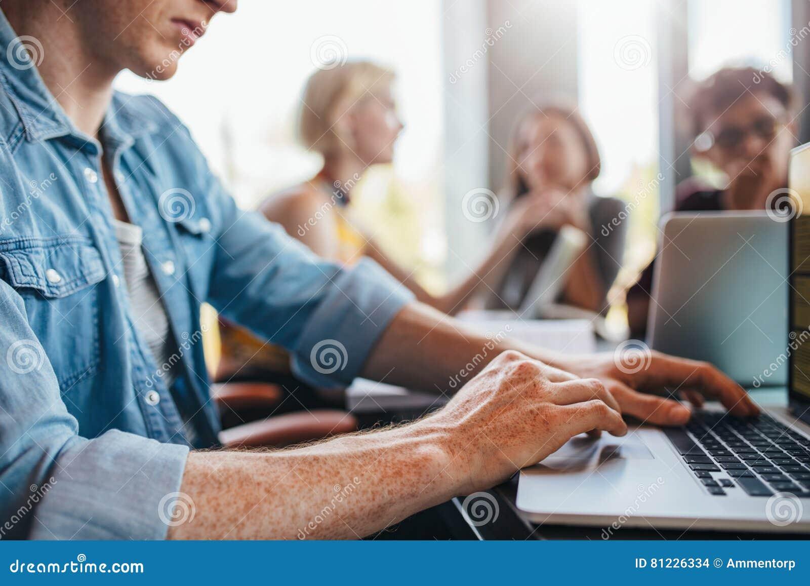 Jonge mens die laptop met klasgenoten met behulp van die op achtergrond bestuderen