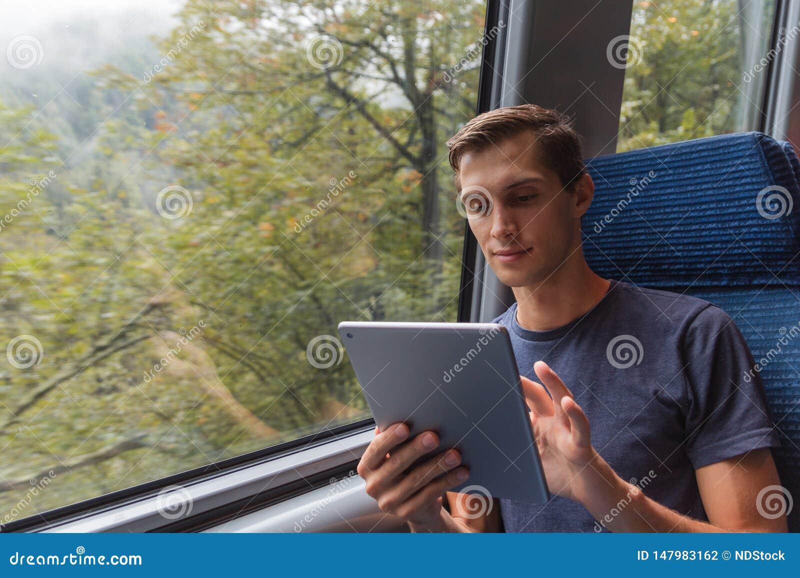 Jonge mens die met een tablet bestuderen terwijl het reizen door trein