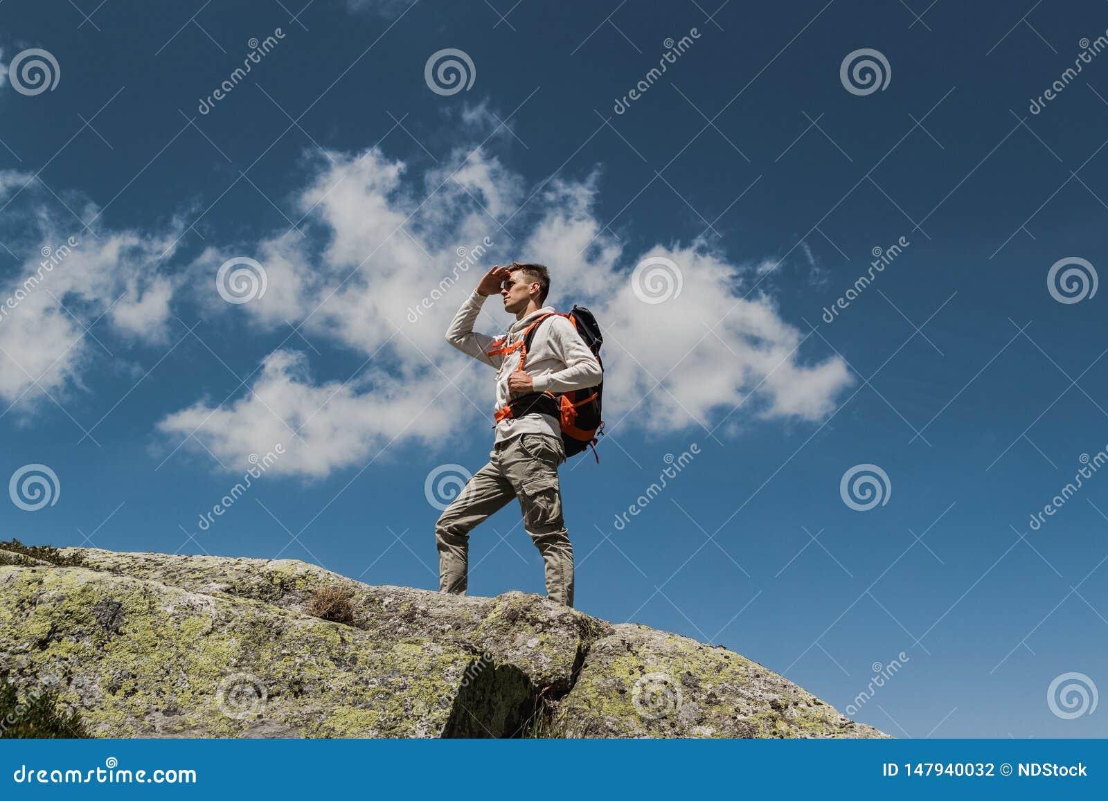 Jonge mens die met grote rugzak de bovenkant van de berg tijdens een zonnige dag lopen te bereiken het overwegen van het panorama