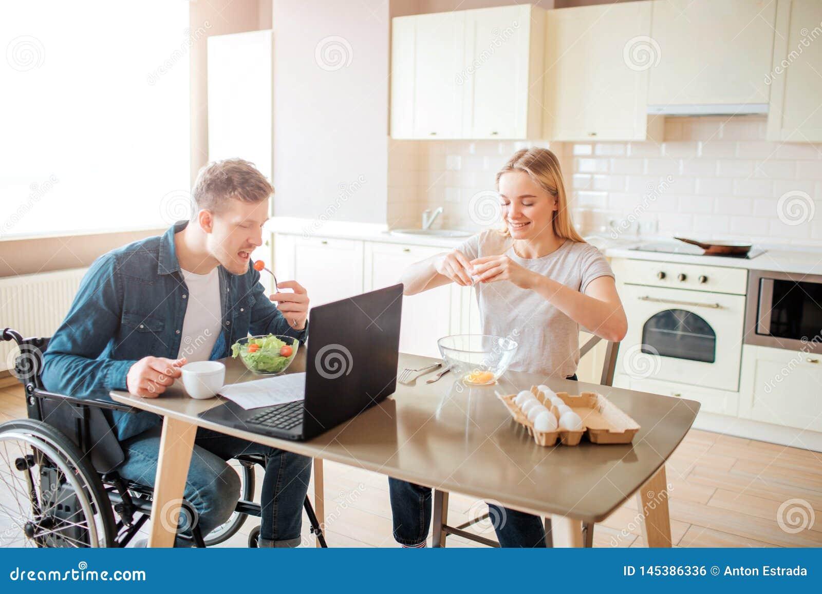 Jonge mens die met inclusiviteit en speciale behoeften salade in keuken eten Zit bij rolstoel en het bestuderen De jonge Vrouw zi