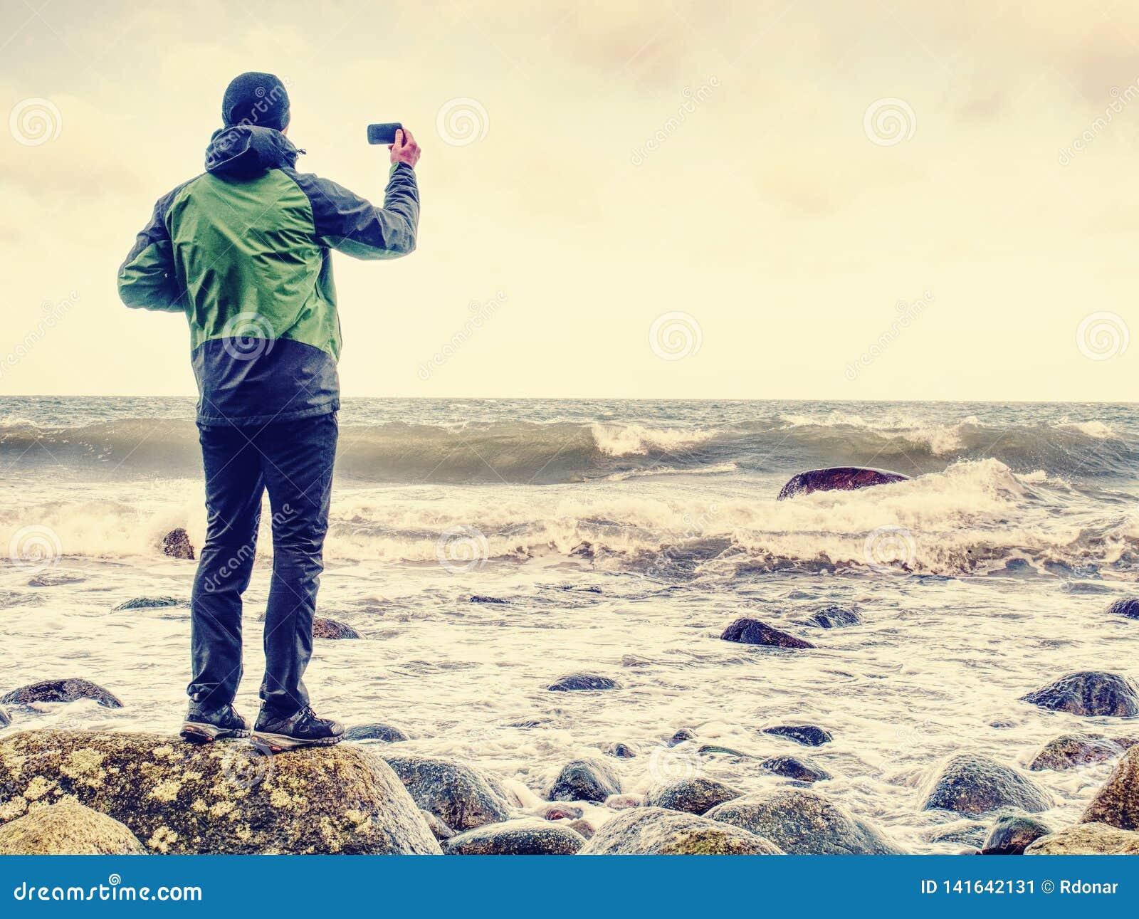 Jonge mens die met toeristisch kostuum op verbazend zeegezicht kijken