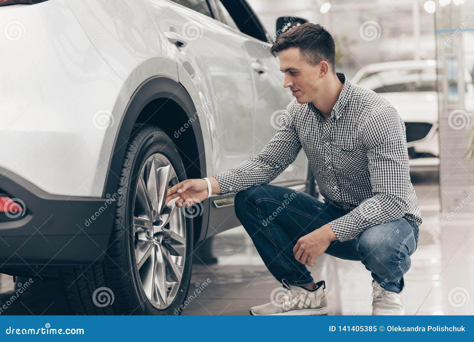 Jonge mens die nieuwe auto kopen bij het handel drijven
