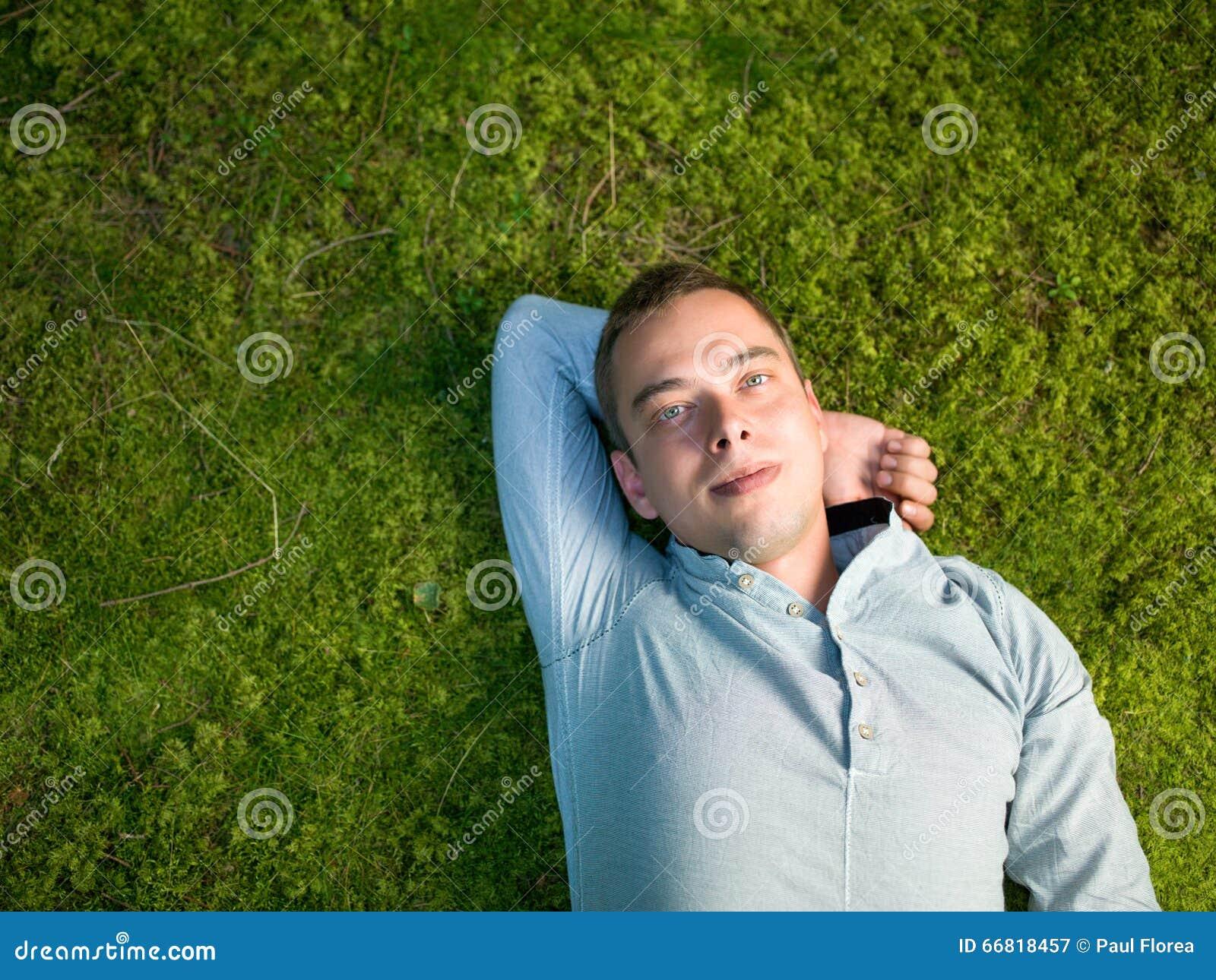 Jonge mens die op groen mos liggen